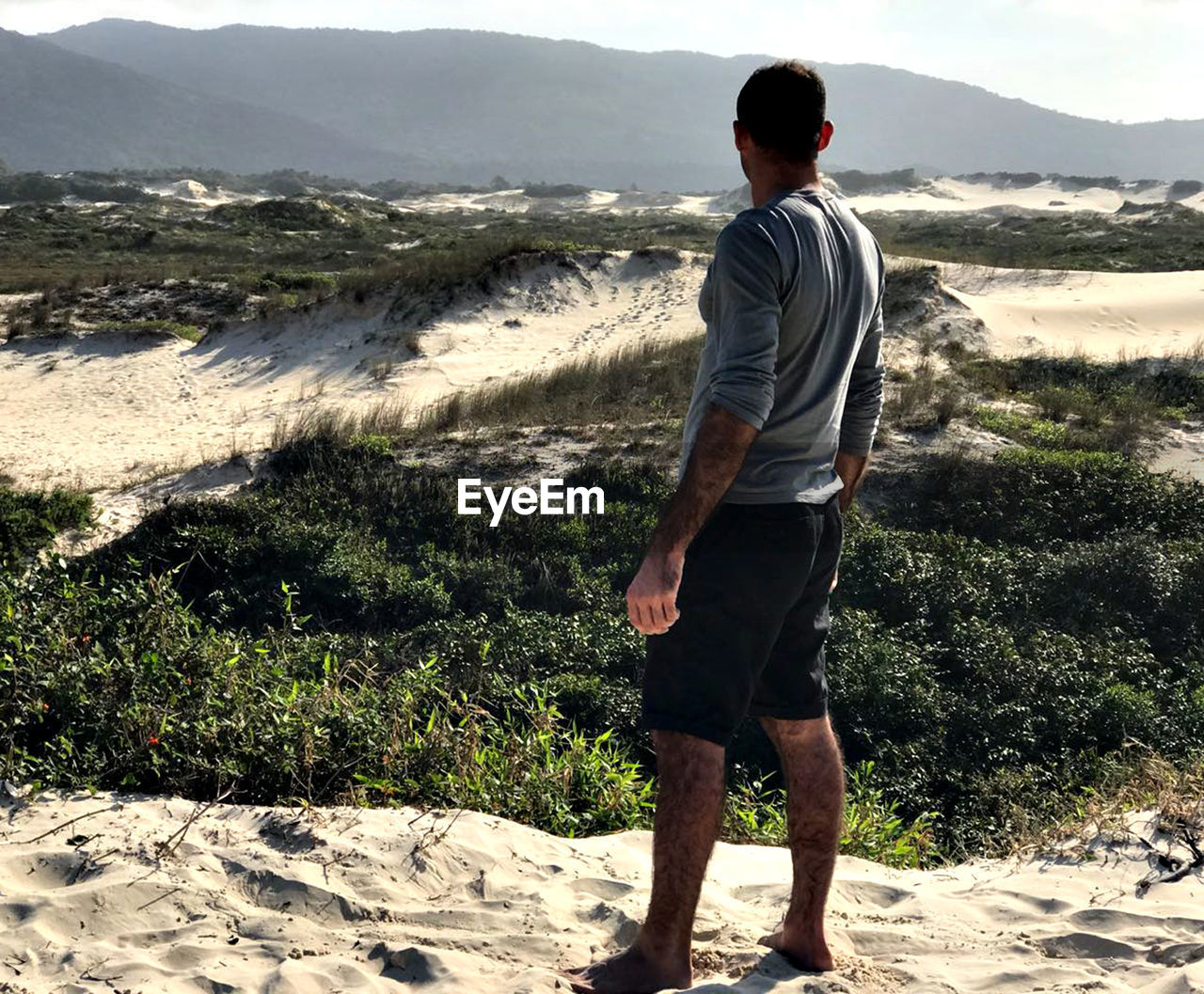 one person, casual clothing, standing, real people, leisure activity, mountain, lifestyles, full length, nature, plant, land, young men, beauty in nature, scenics - nature, day, sunlight, men, non-urban scene, outdoors, shorts, looking at view
