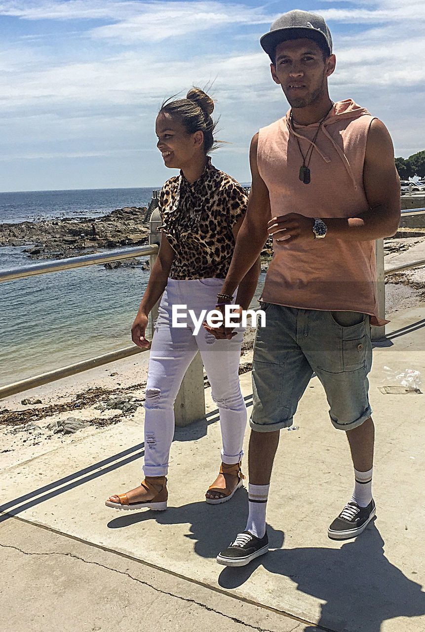 two people, sea, togetherness, casual clothing, full length, cloud - sky, water, sunlight, sky, young women, standing, young adult, day, outdoors, leisure activity, shadow, young men, beach, real people, vacations, nature, lifestyles, horizon over water, happiness, smiling, friendship, adult, people, adults only
