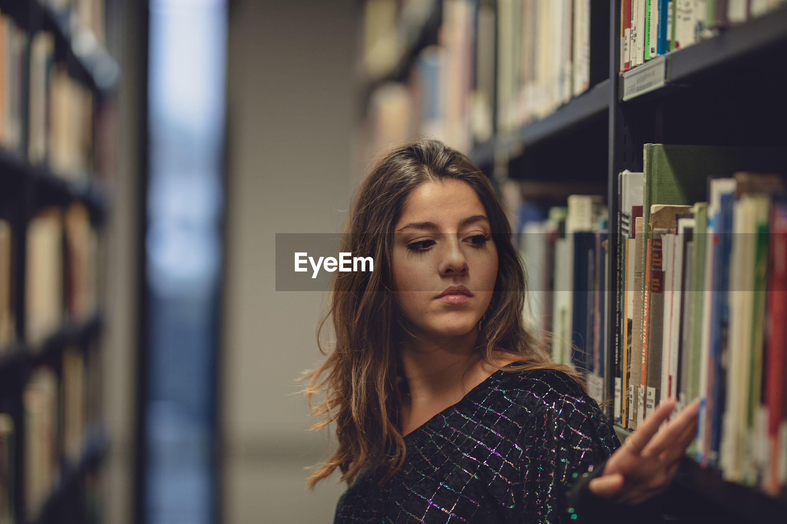Young woman standing by bookshelf at library