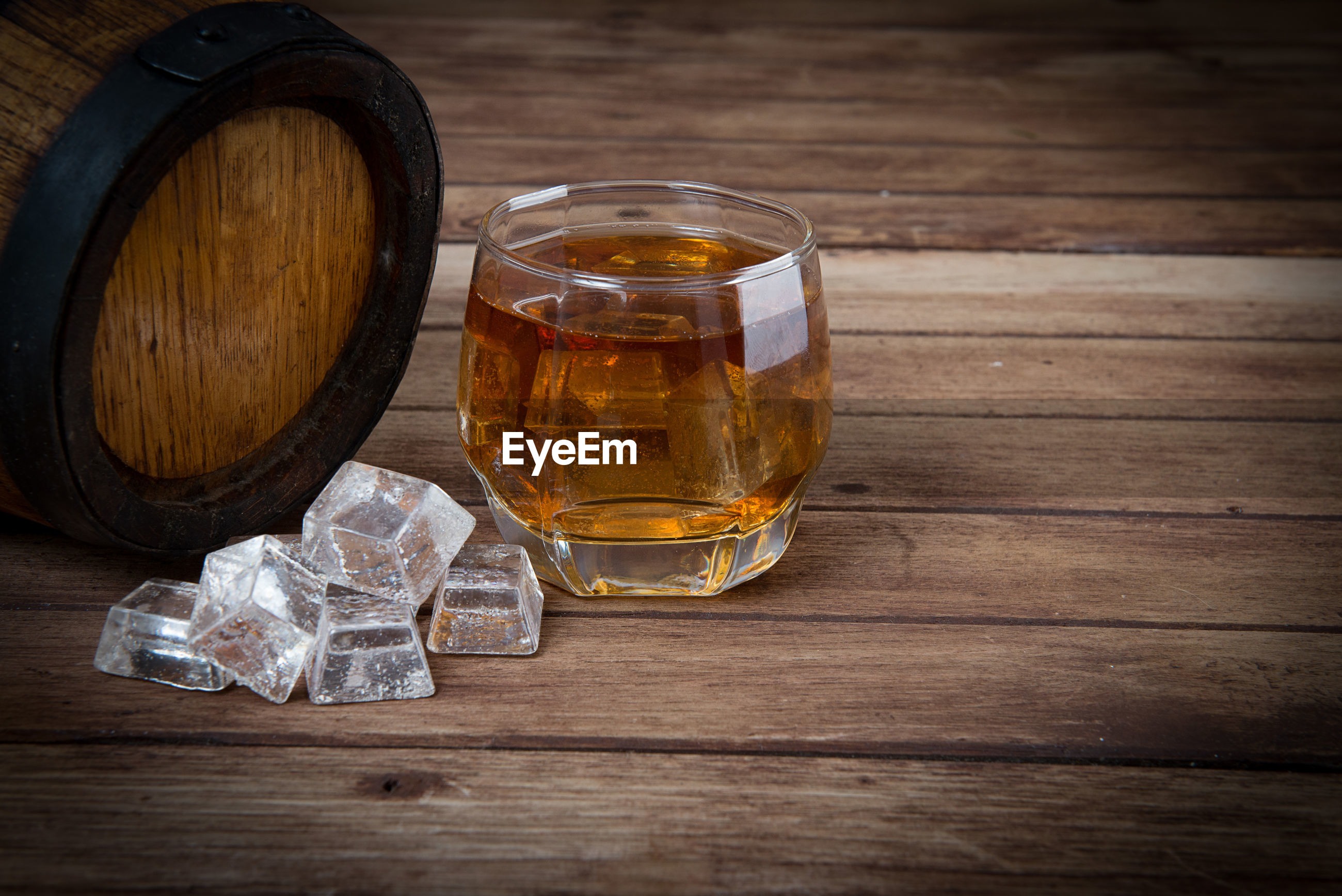 Close-up of ice cubes and whiskey in glass on table