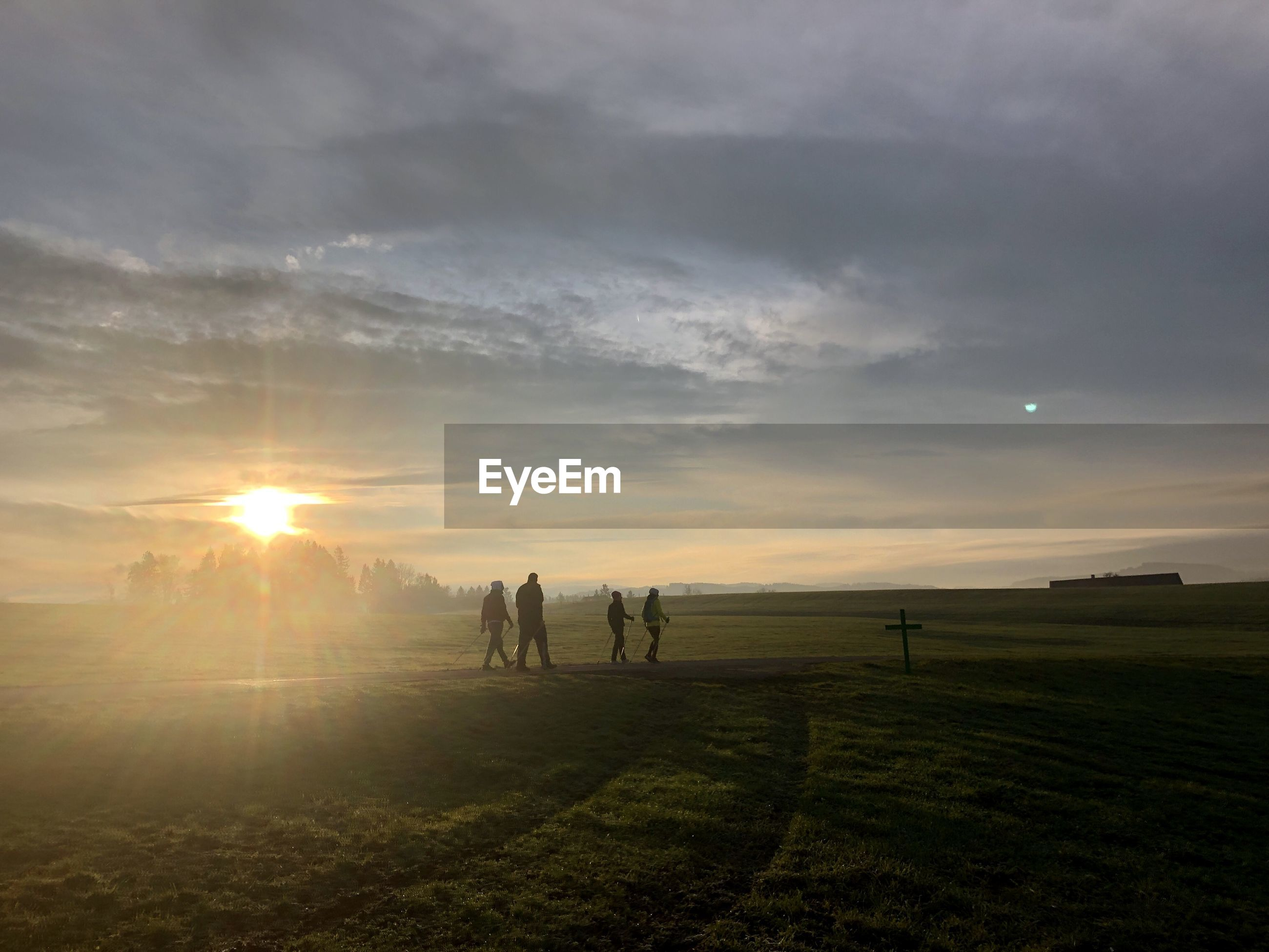 PEOPLE ON FIELD AT SUNSET
