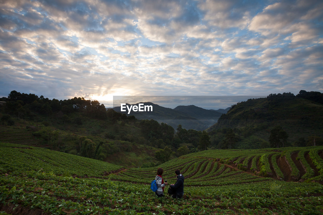 People in farm against cloudy sky