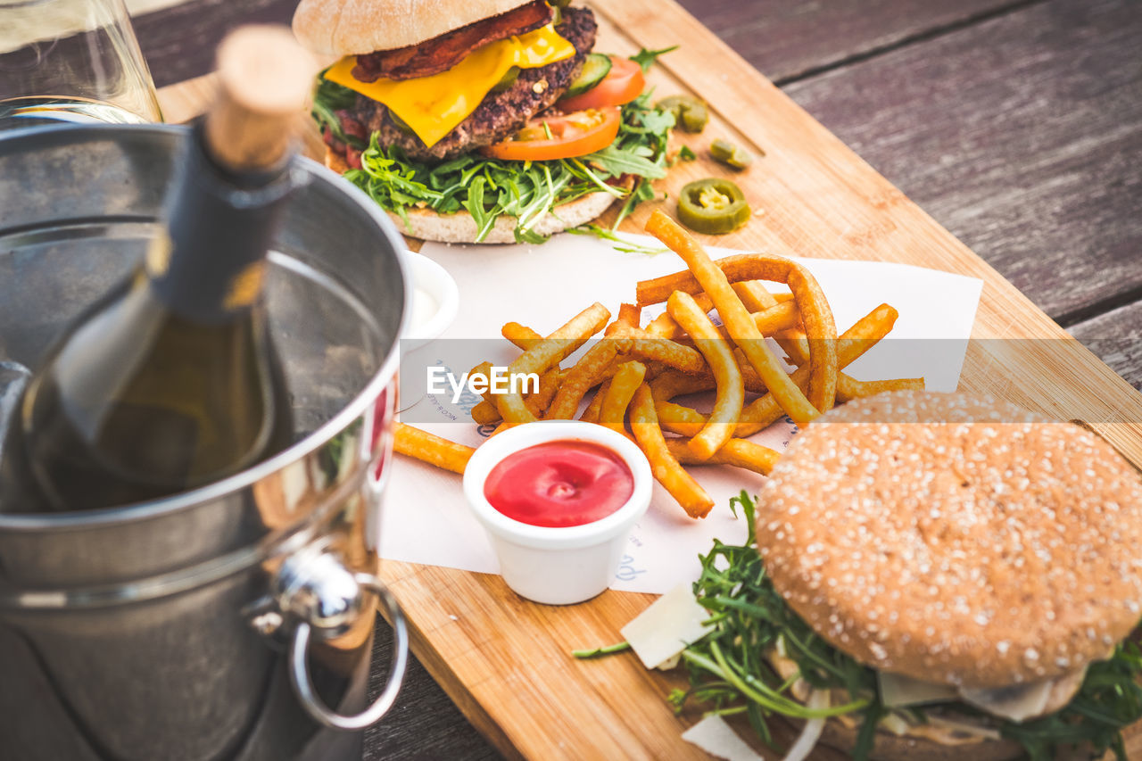 food and drink, fast food, food, ready-to-eat, burger, french fries, potato, prepared potato, sandwich, unhealthy eating, table, still life, fried, hamburger, freshness, vegetable, high angle view, indoors, bread, meat, no people, relish, snack, onion ring, glass, tray