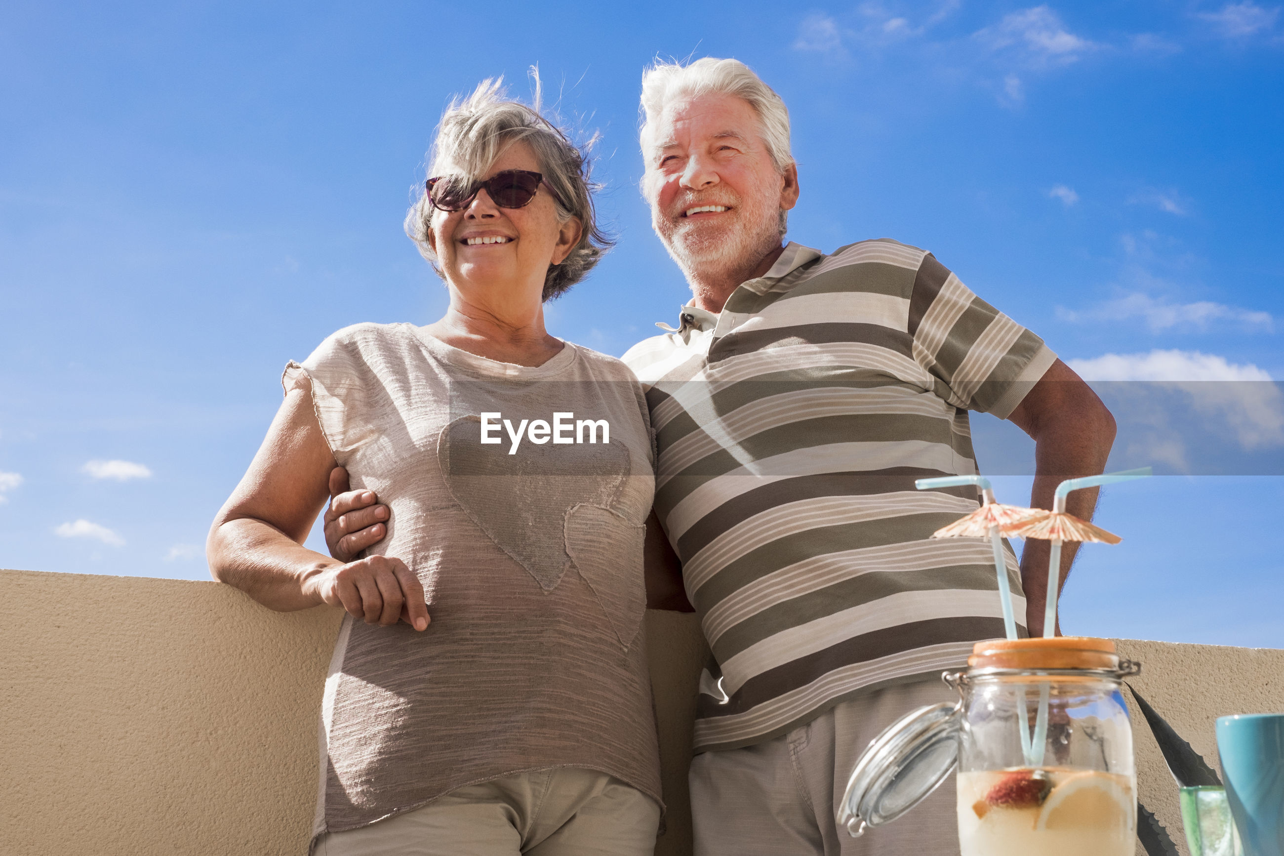 Low angle view of senior couple smiling while standing against blue sky