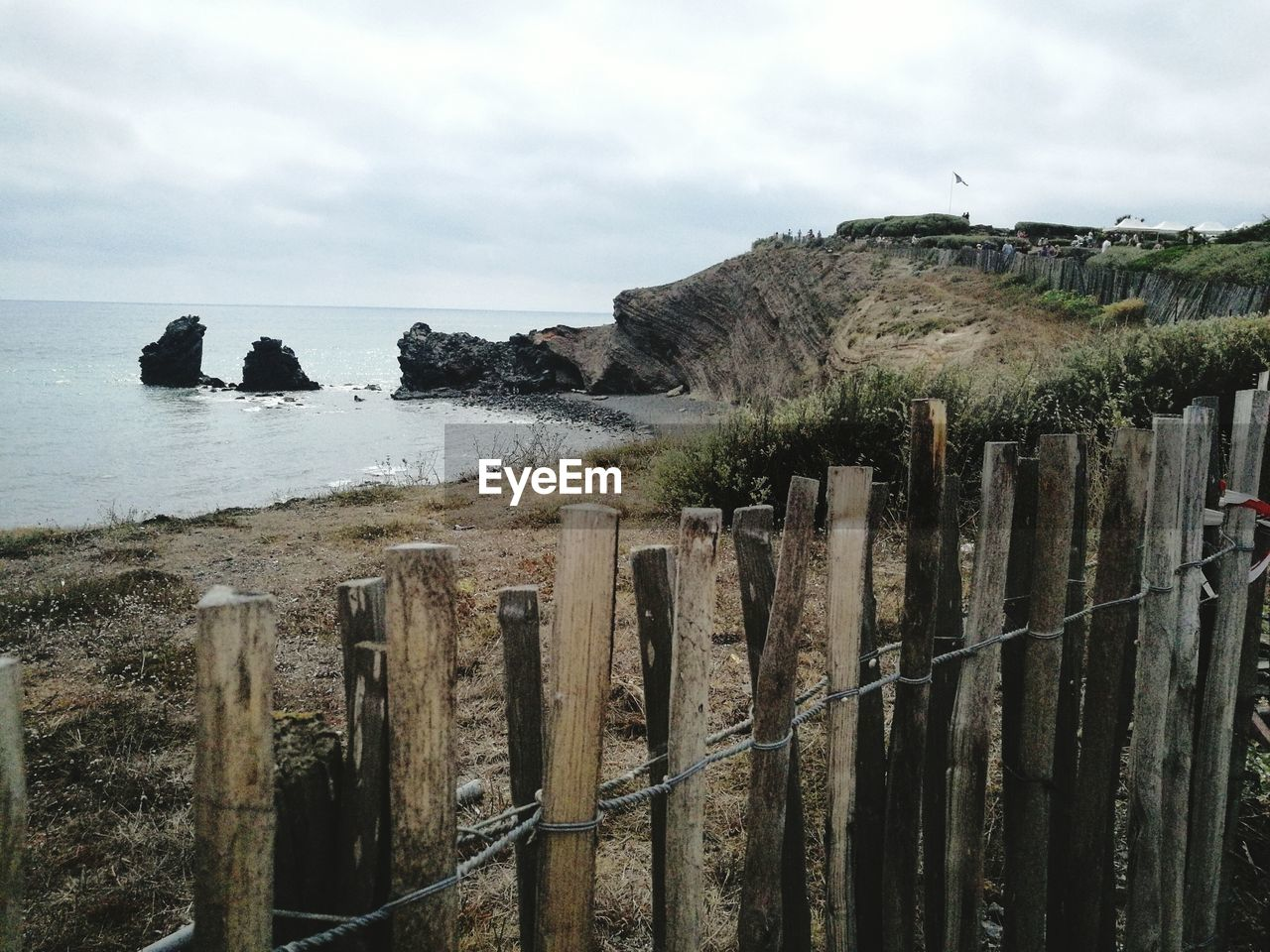 Wooden Posts On Cliff By Sea Against Sky