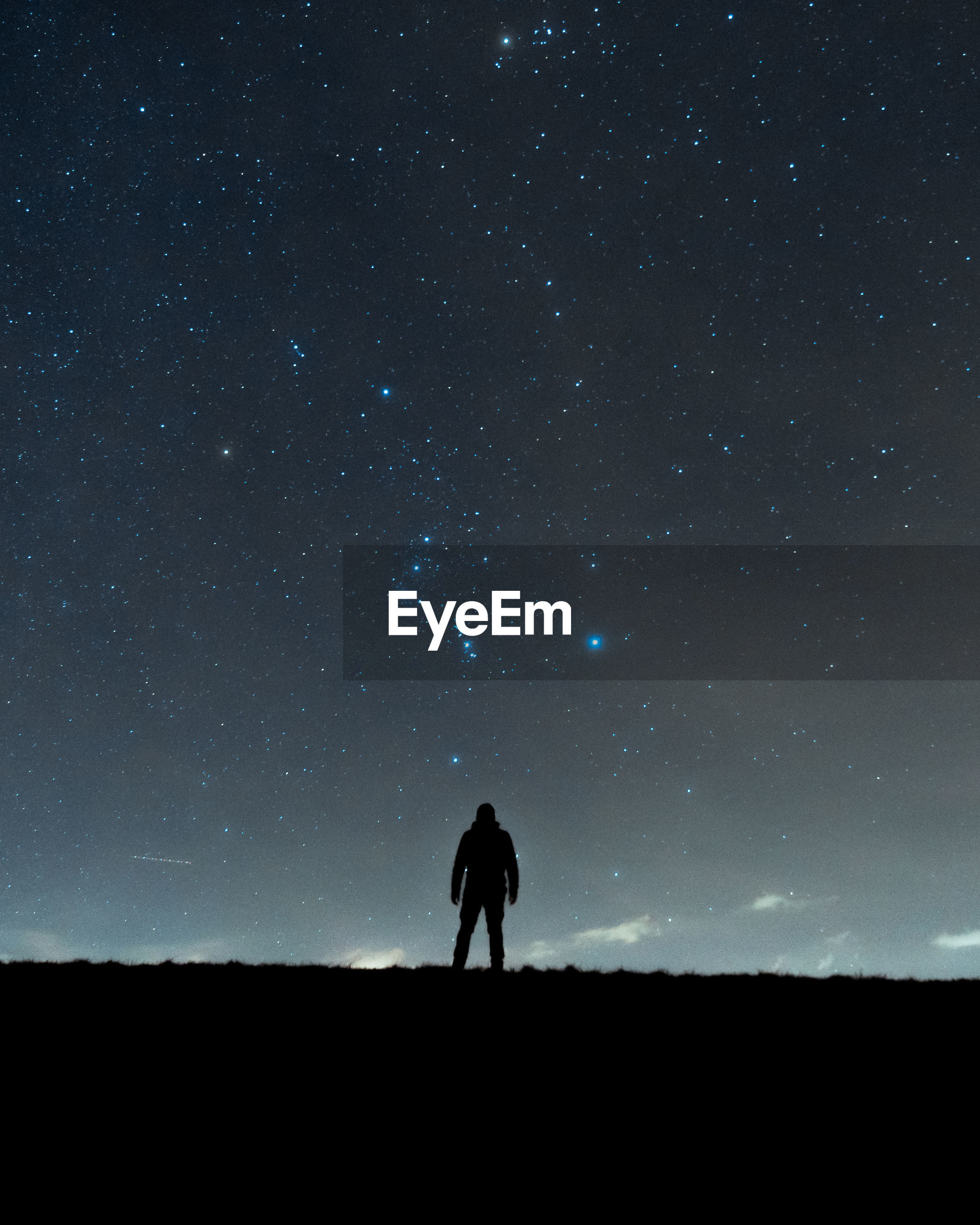 Silhouette man standing on field against sky at night