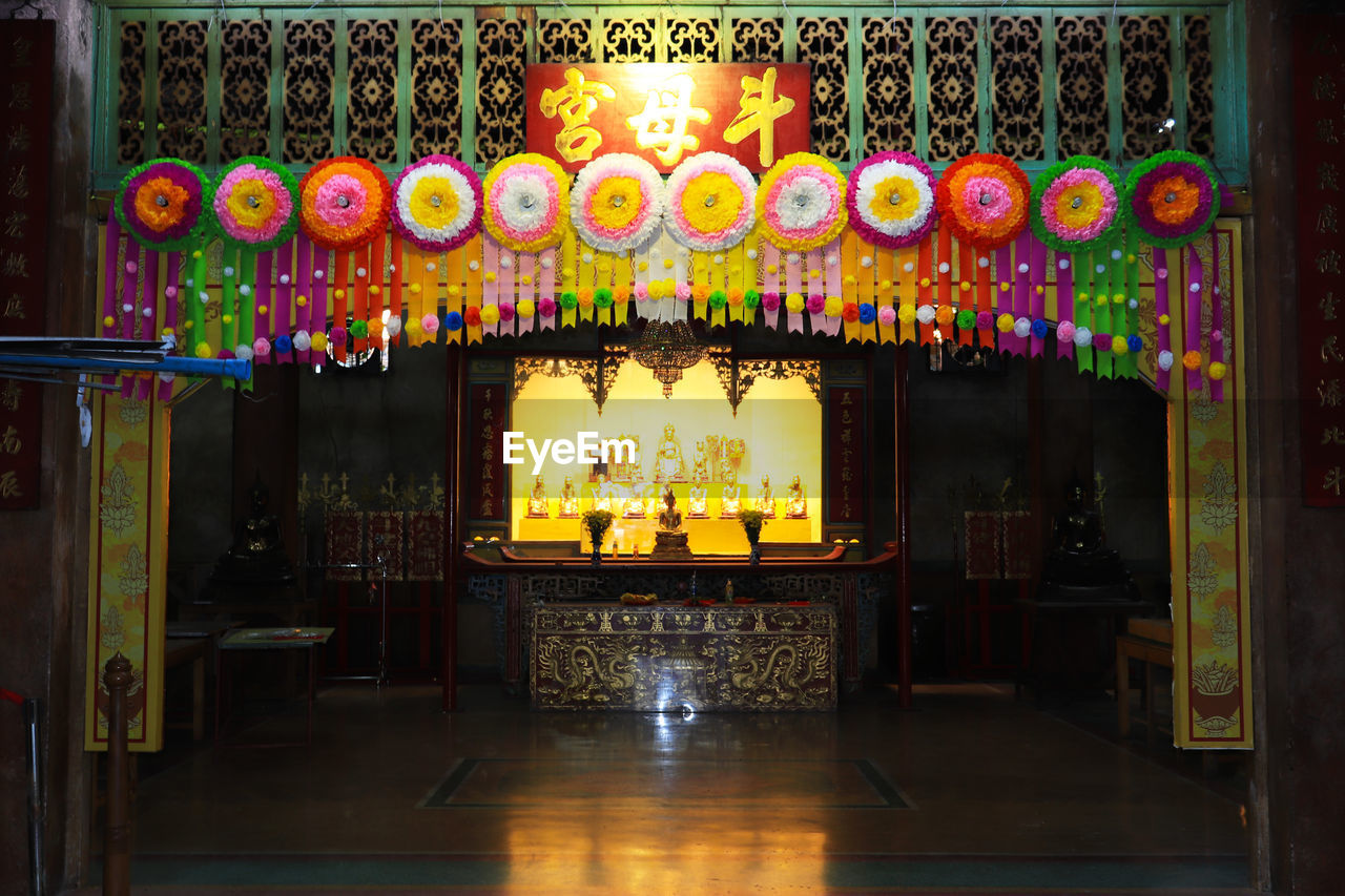illuminated, lighting equipment, no people, indoors, architecture, built structure, multi colored, glowing, decoration, night, building, entrance, ornate, place of worship, religion, lantern, door, floral pattern