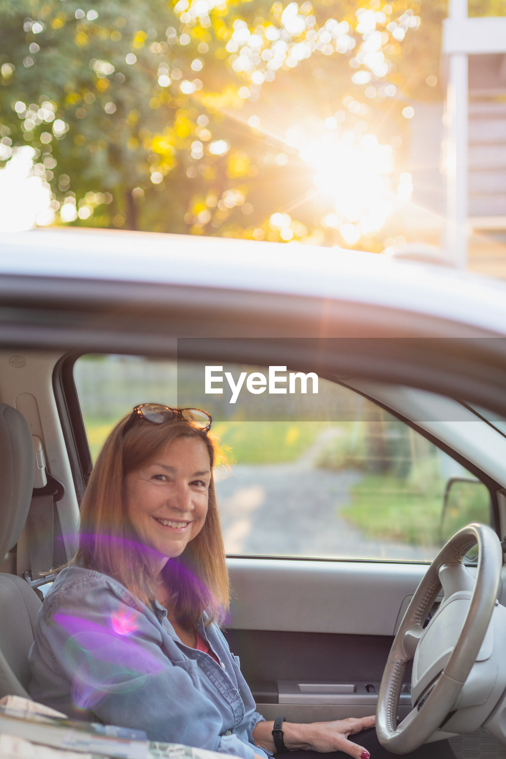 Portrait of mature woman smiling while driving car during sunset