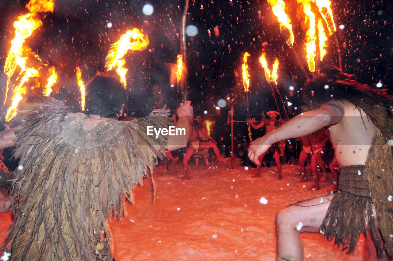 PANORAMIC VIEW OF PEOPLE AT NIGHT DURING RAINY SEASON