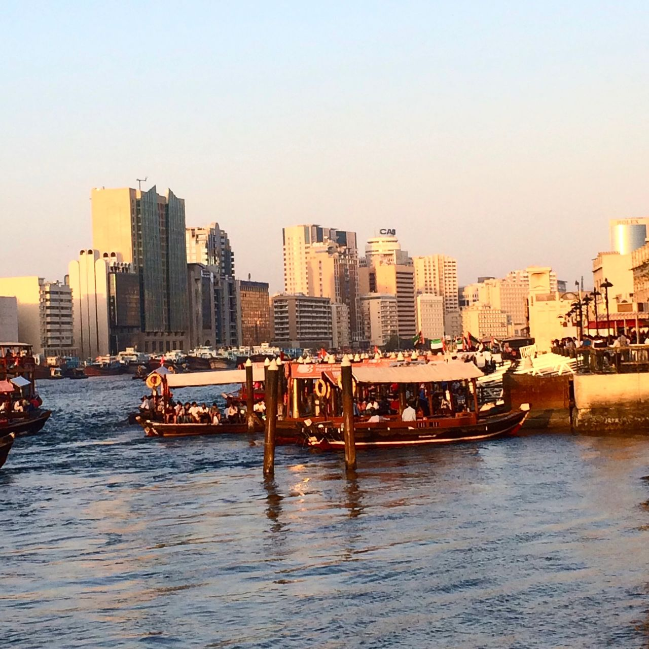 architecture, building exterior, water, waterfront, built structure, city, sea, clear sky, outdoors, cityscape, skyscraper, nautical vessel, city life, day, sky, large group of people, real people, urban skyline, nature