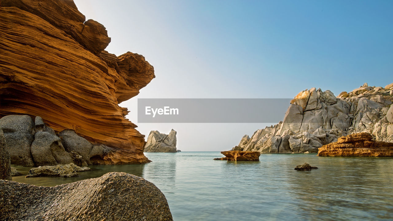 Scenic View Of Rock Formations And Sea Against Sky
