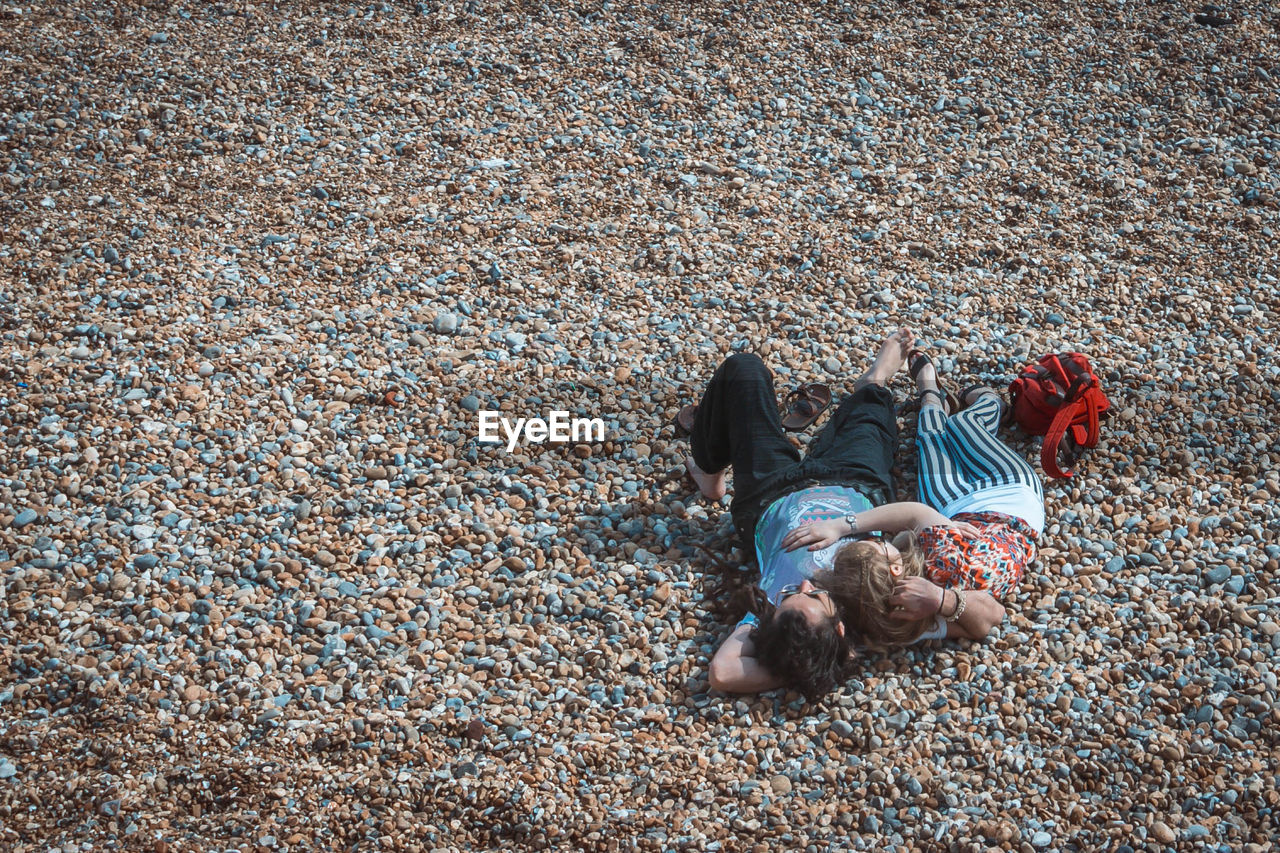 High Angle View Of Couple Relaxing On Pebbles At Beach