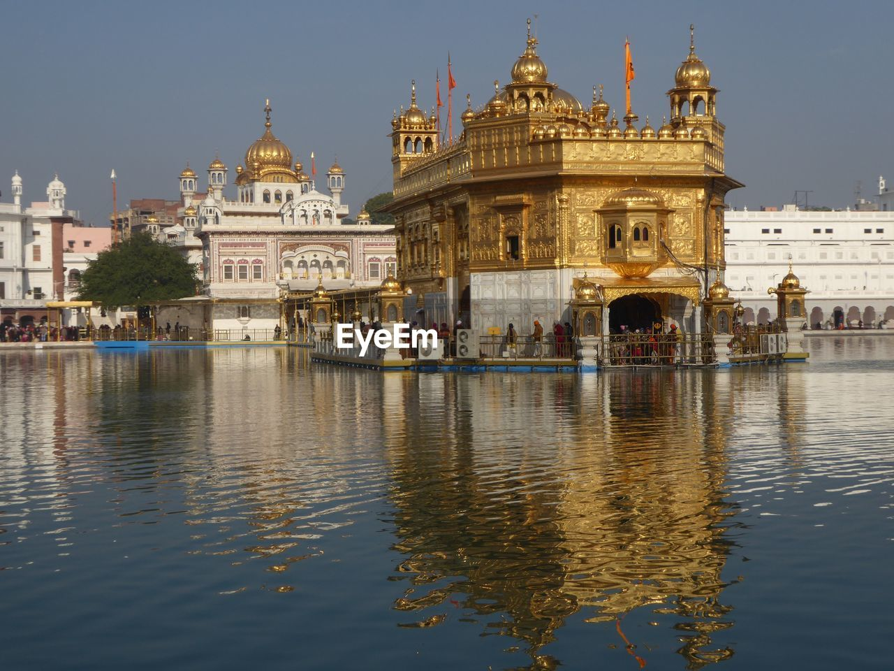 Reflection of golden temple in lake against sky