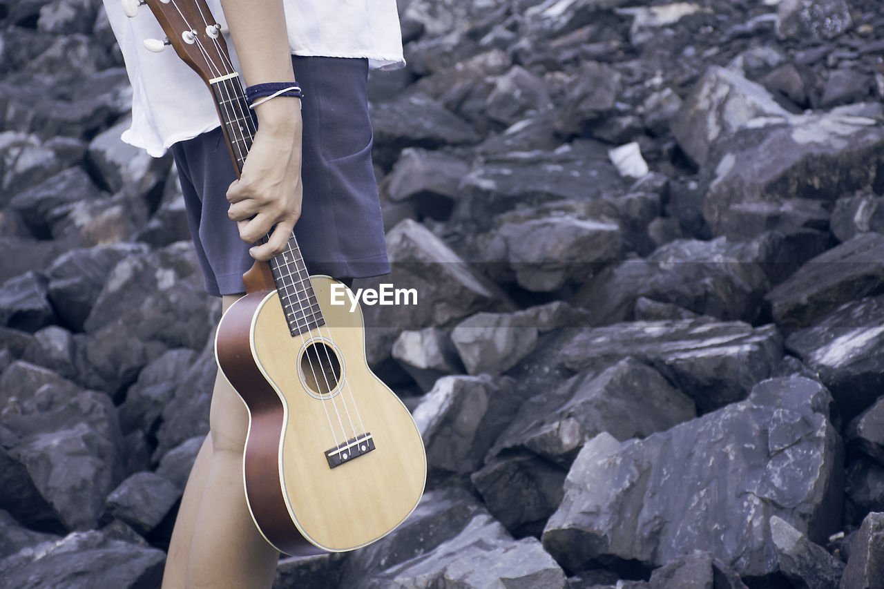 Midsection Of Man Holding Guitar On Rocks