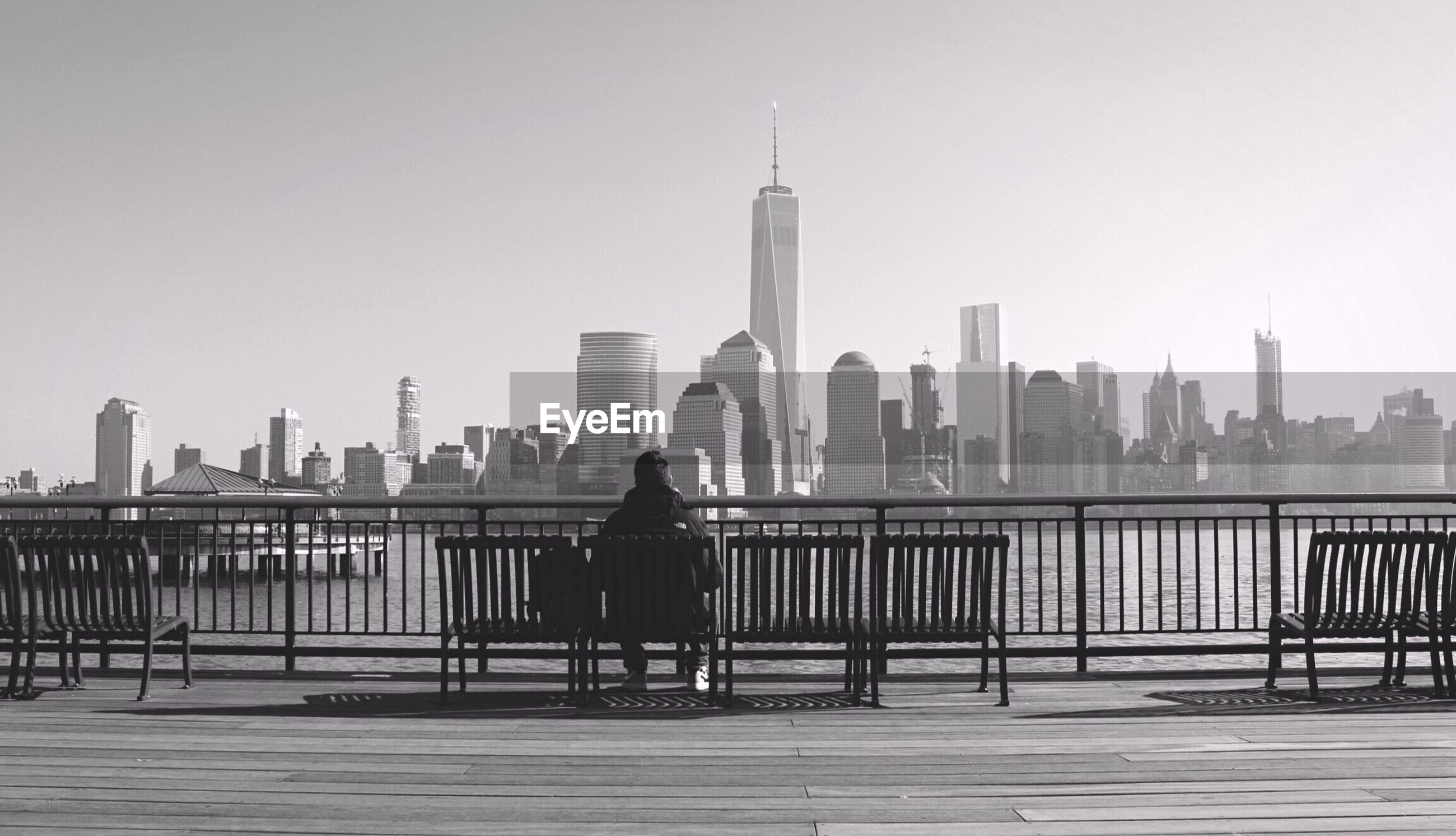 Rear view of man sitting on bench against one world trade center in city