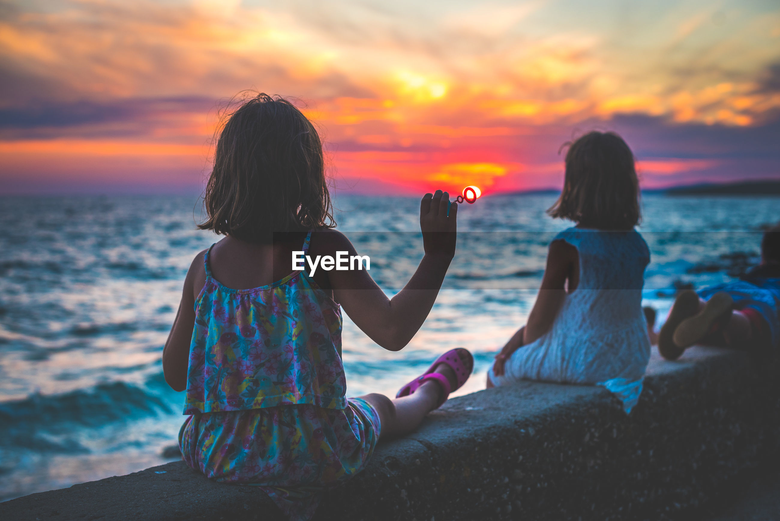 Girls sitting on retaining wall against sky during sunset
