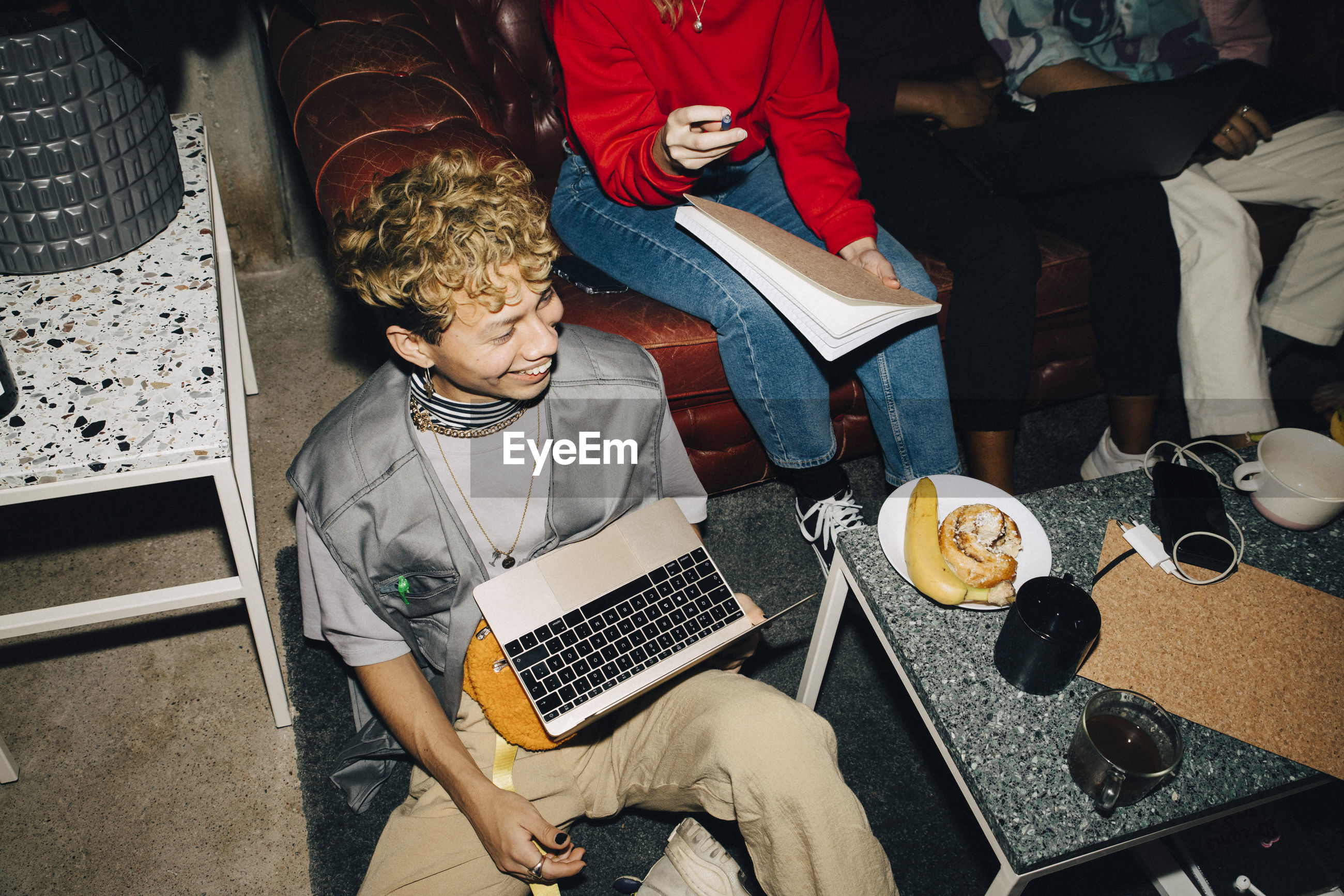 HIGH ANGLE VIEW OF FRIENDS SITTING ON LAPTOP