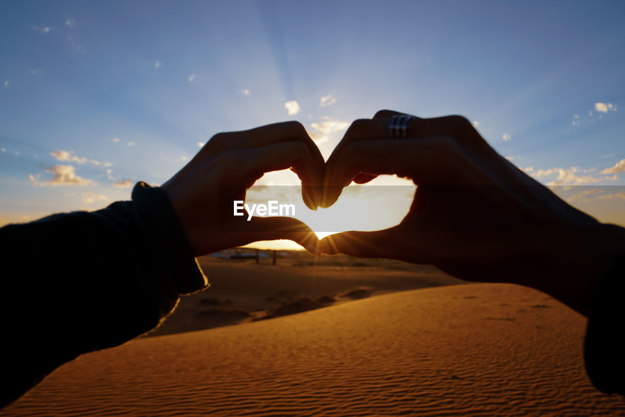 human hand, hand, human body part, sky, love, heart shape, sunset, positive emotion, lifestyles, real people, emotion, one person, sunlight, nature, body part, leisure activity, making, focus on foreground, personal perspective, finger, sun, couple - relationship, outdoors