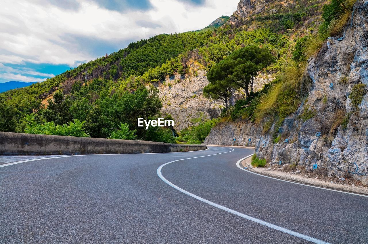 road, mountain, transportation, sky, cloud - sky, plant, scenics - nature, no people, beauty in nature, symbol, direction, nature, the way forward, tranquility, marking, sign, tree, day, road marking, tranquil scene, mountain range, outdoors, surface level, formation