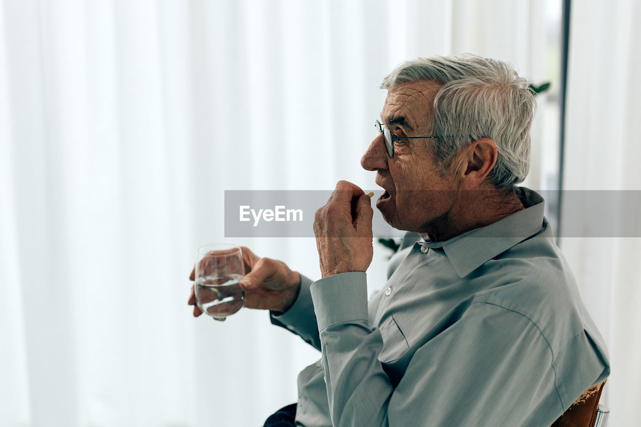 Old man taking pill. senior person holding a glass water ready to swallow medication.