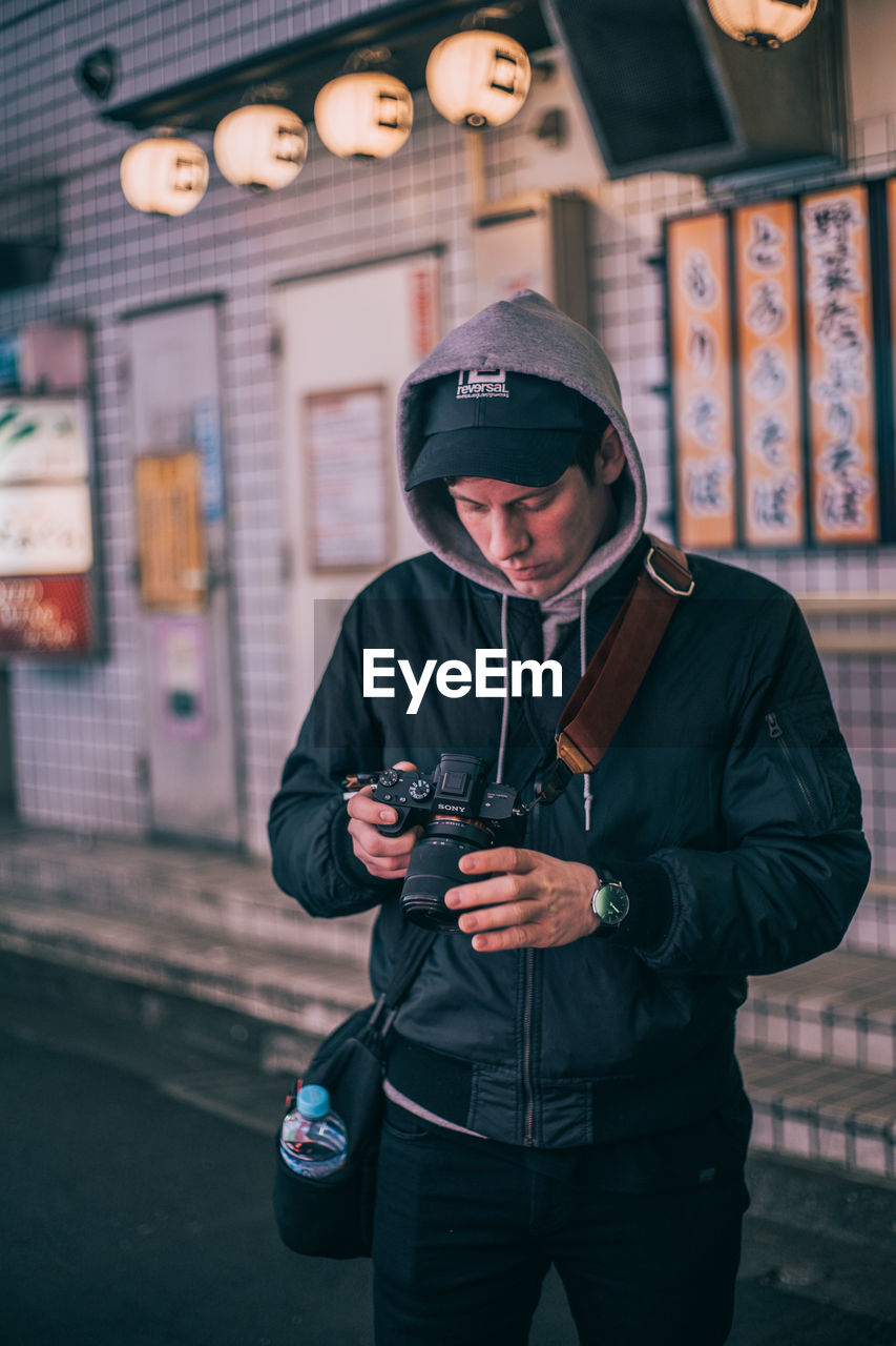 one person, real people, communication, technology, clothing, standing, front view, lifestyles, young adult, three quarter length, men, holding, focus on foreground, young men, leisure activity, mobile phone, architecture, males, jacket, wireless technology, outdoors, warm clothing