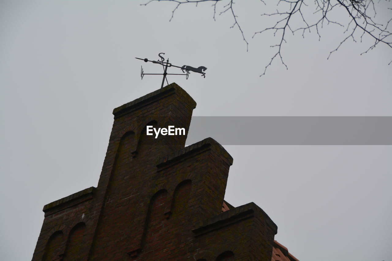 low angle view, weather vane, guidance, direction, architecture, day, religion, outdoors, clear sky, no people, building exterior, spirituality, built structure, place of worship, sky