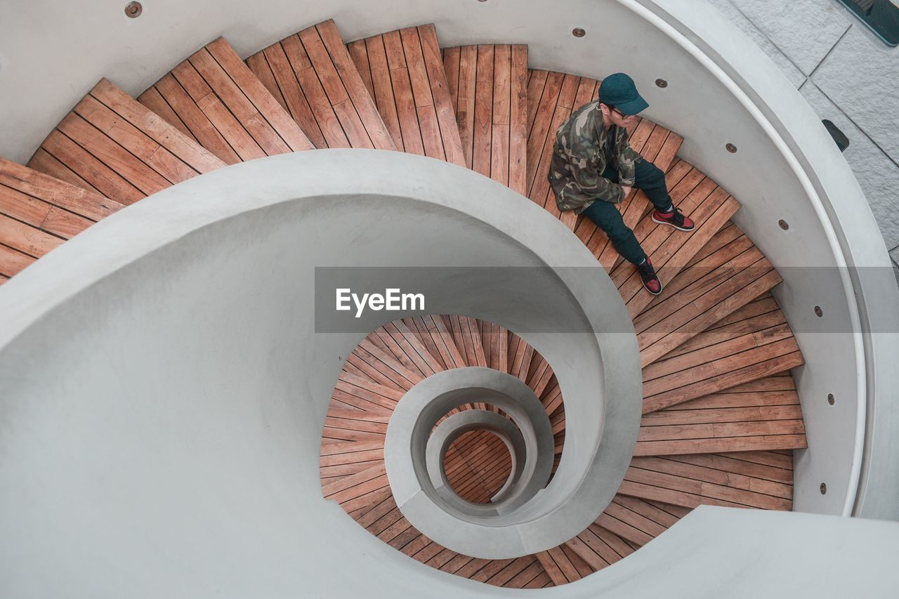 real people, high angle view, one person, architecture, men, indoors, wood - material, full length, day, built structure, lifestyles, leisure activity, directly above, staircase, steps and staircases, casual clothing, women, adult