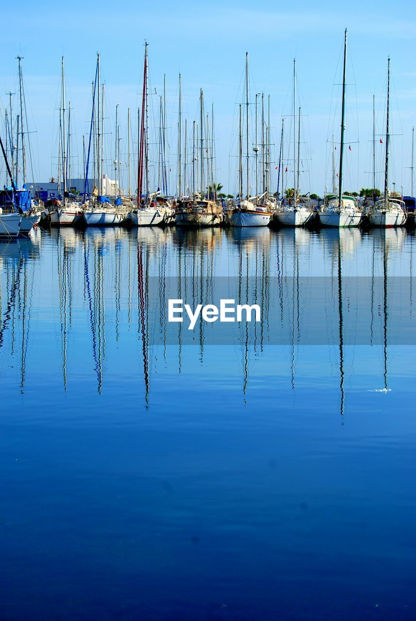 water, moored, nautical vessel, reflection, mode of transport, transportation, no people, nature, mast, sky, outdoors, day, scenics, tranquility, harbor, blue, sailboat, beauty in nature
