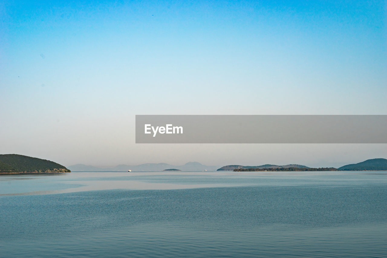 water, scenics - nature, sea, beauty in nature, sky, tranquil scene, tranquility, waterfront, copy space, mountain, clear sky, idyllic, no people, nature, non-urban scene, blue, outdoors, day, land