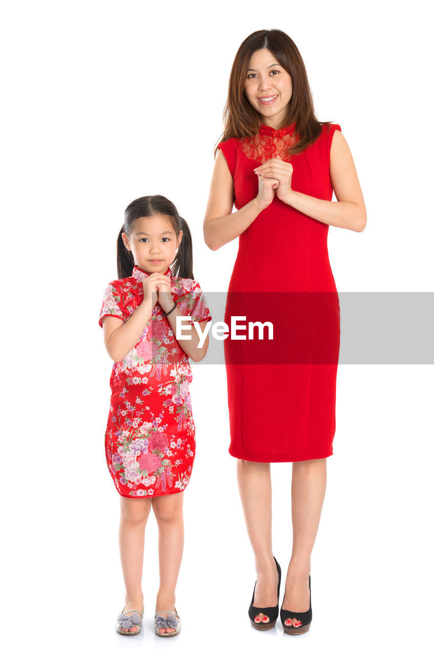 Portrait of smiling mother and daughter in traditional clothing gesturing while standing against white background