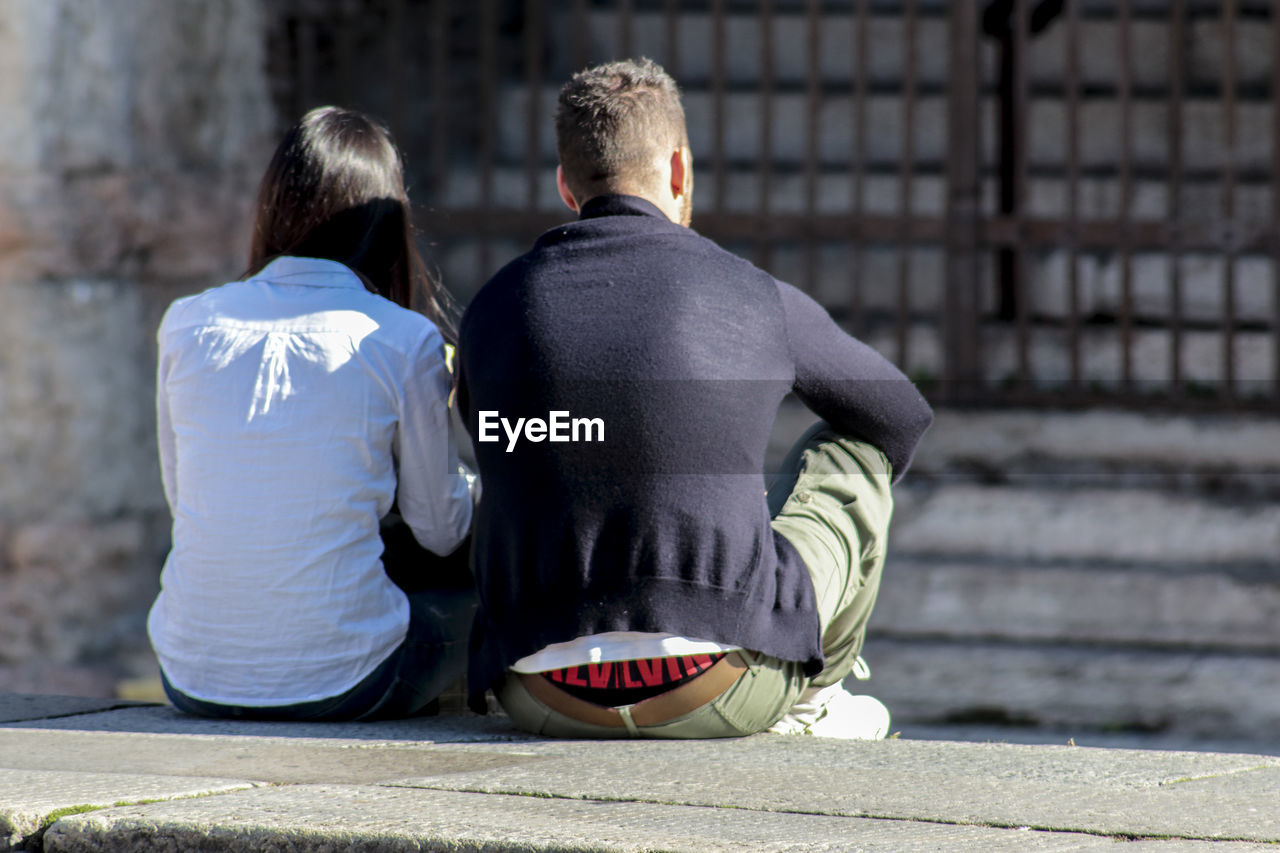 Rear view of couple sitting outdoors