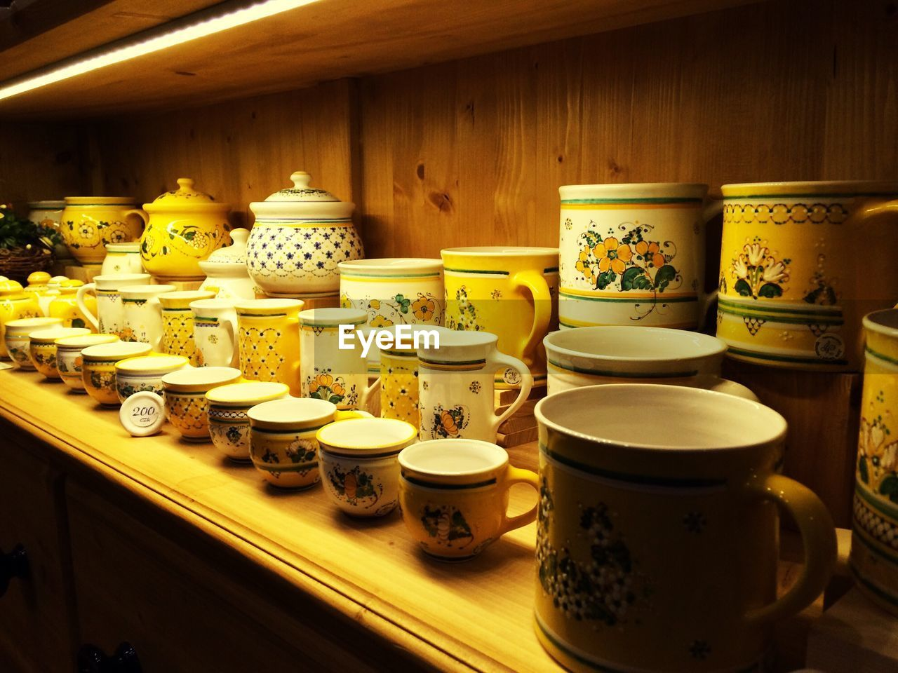 shelf, no people, indoors, plate, variation, container, food and drink, large group of objects, teapot, bowl, arrangement, yellow, food, day, close-up