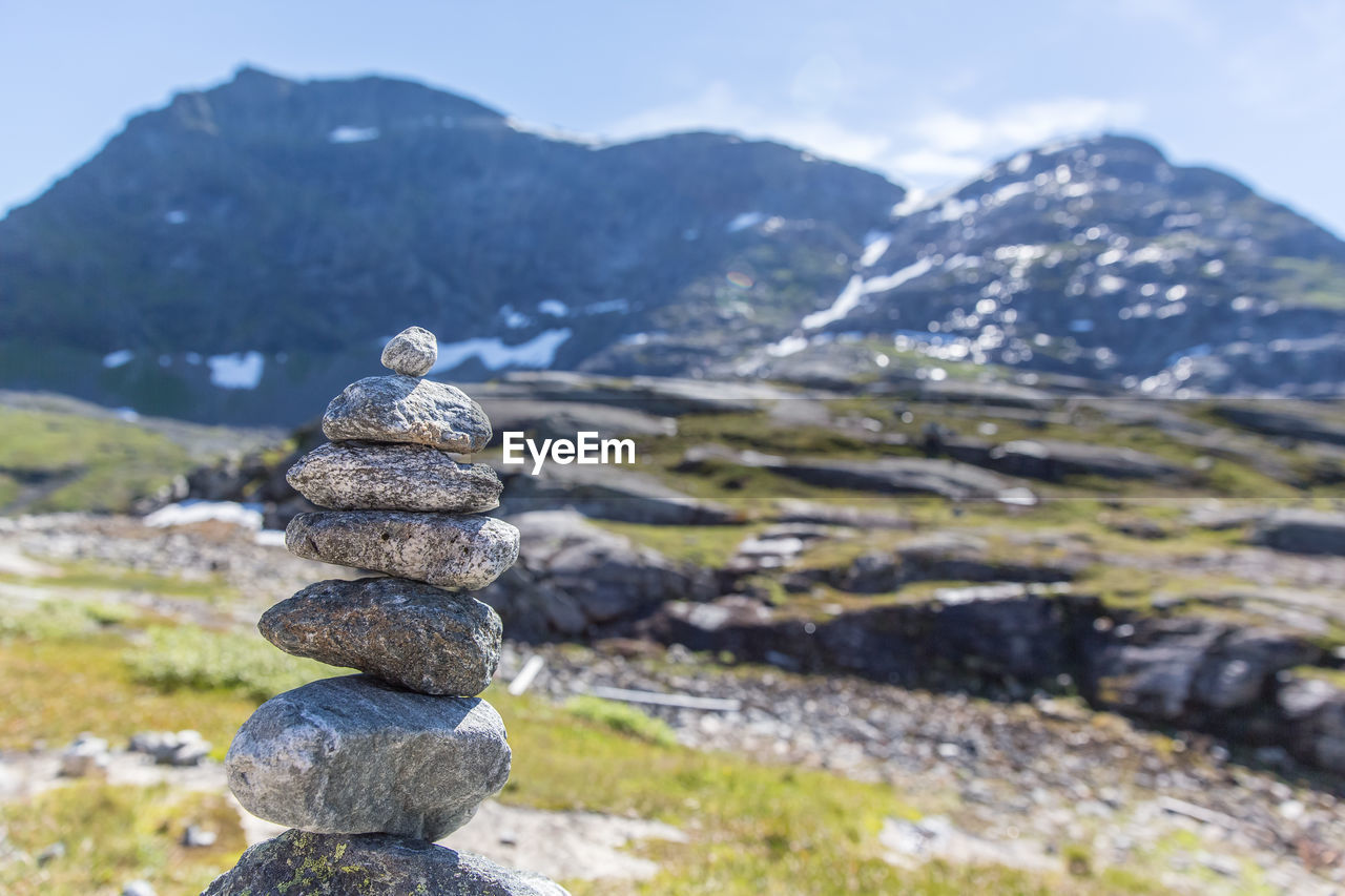 mountain, balance, stack, scenics - nature, solid, beauty in nature, rock, nature, tranquil scene, zen-like, stone - object, tranquility, rock - object, day, focus on foreground, mountain range, no people, non-urban scene, landscape, sky, outdoors, pebble