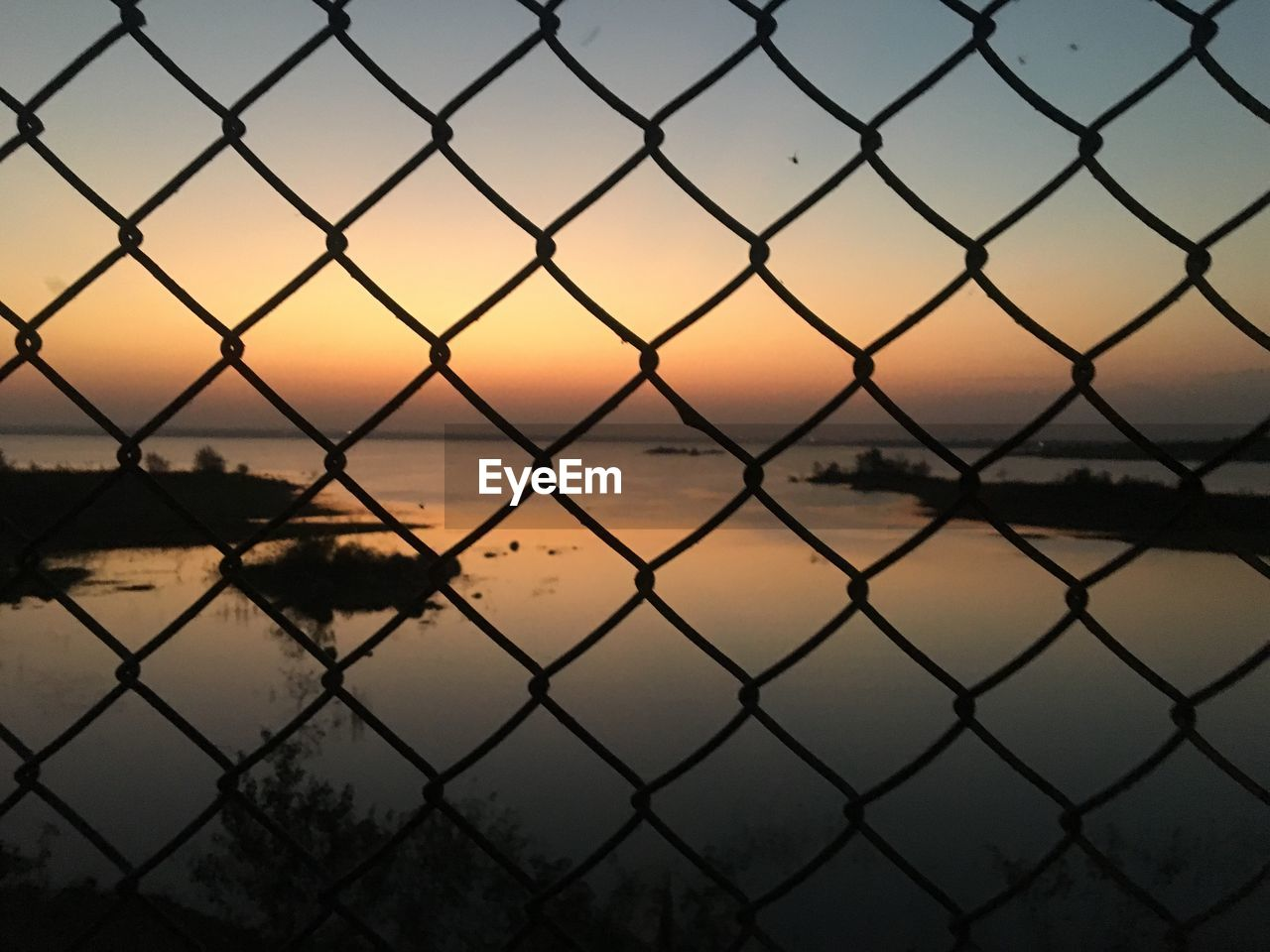 fence, security, safety, barrier, boundary, protection, sky, chainlink fence, sunset, metal, nature, no people, scenics - nature, water, focus on foreground, outdoors, backgrounds, pattern, beauty in nature, crisscross