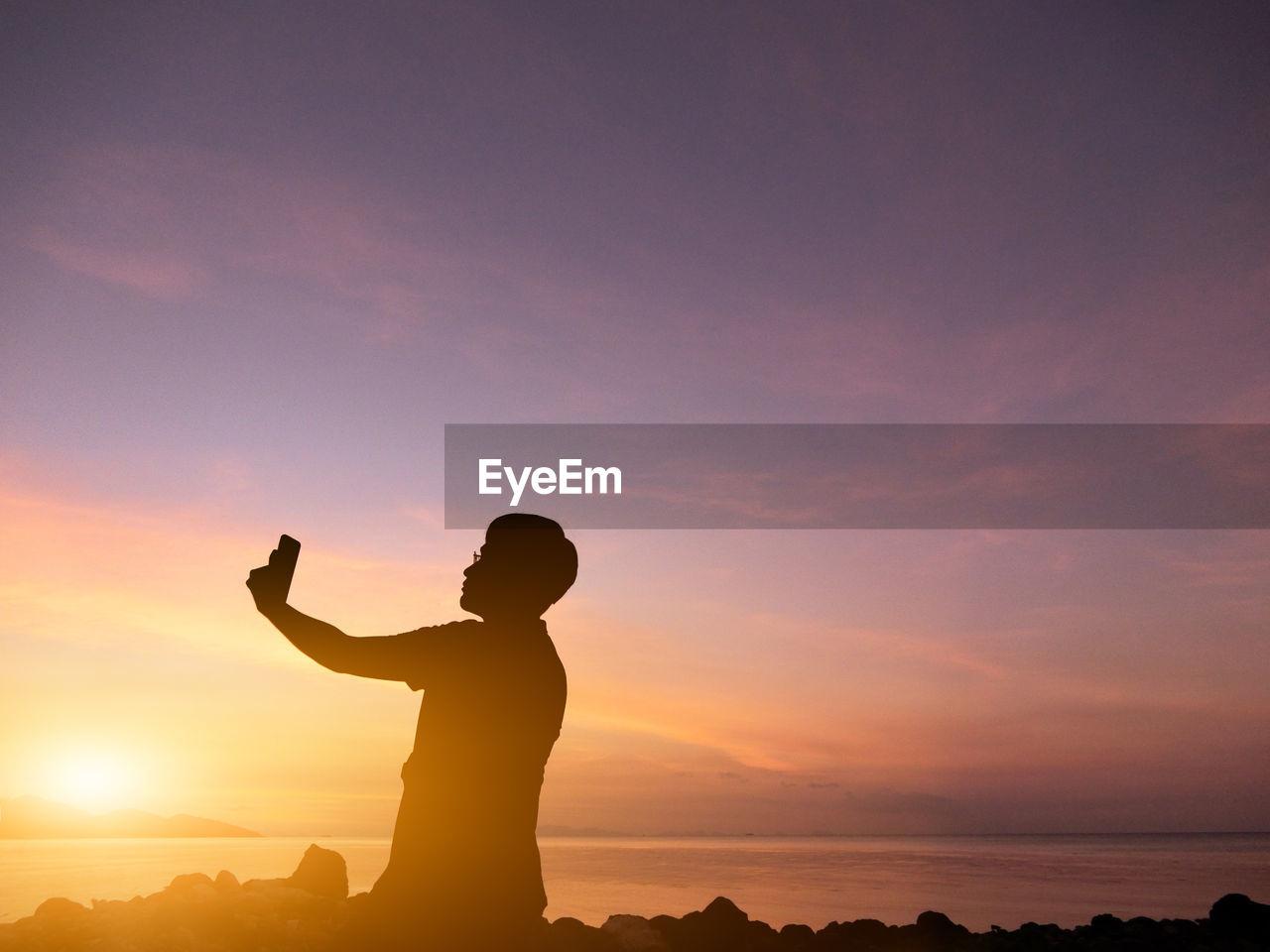 Silhouette Man Taking Selfie At Beach During Sunset