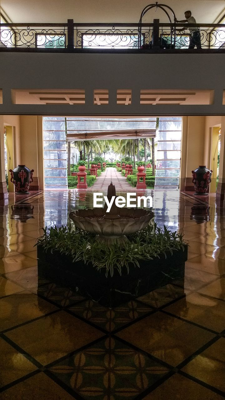 architecture, indoors, flooring, incidental people, built structure, tile, tiled floor, glass - material, business, table, place of worship, building, spirituality, illuminated, travel destinations, potted plant, religion, restaurant, seat, transparent, luxury