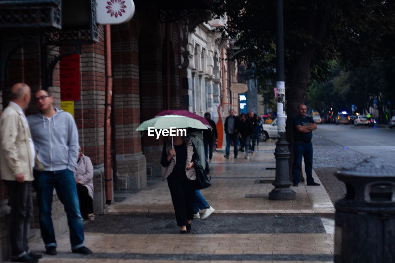 GROUP OF PEOPLE WALKING ON STREET IN RAINY SEASON
