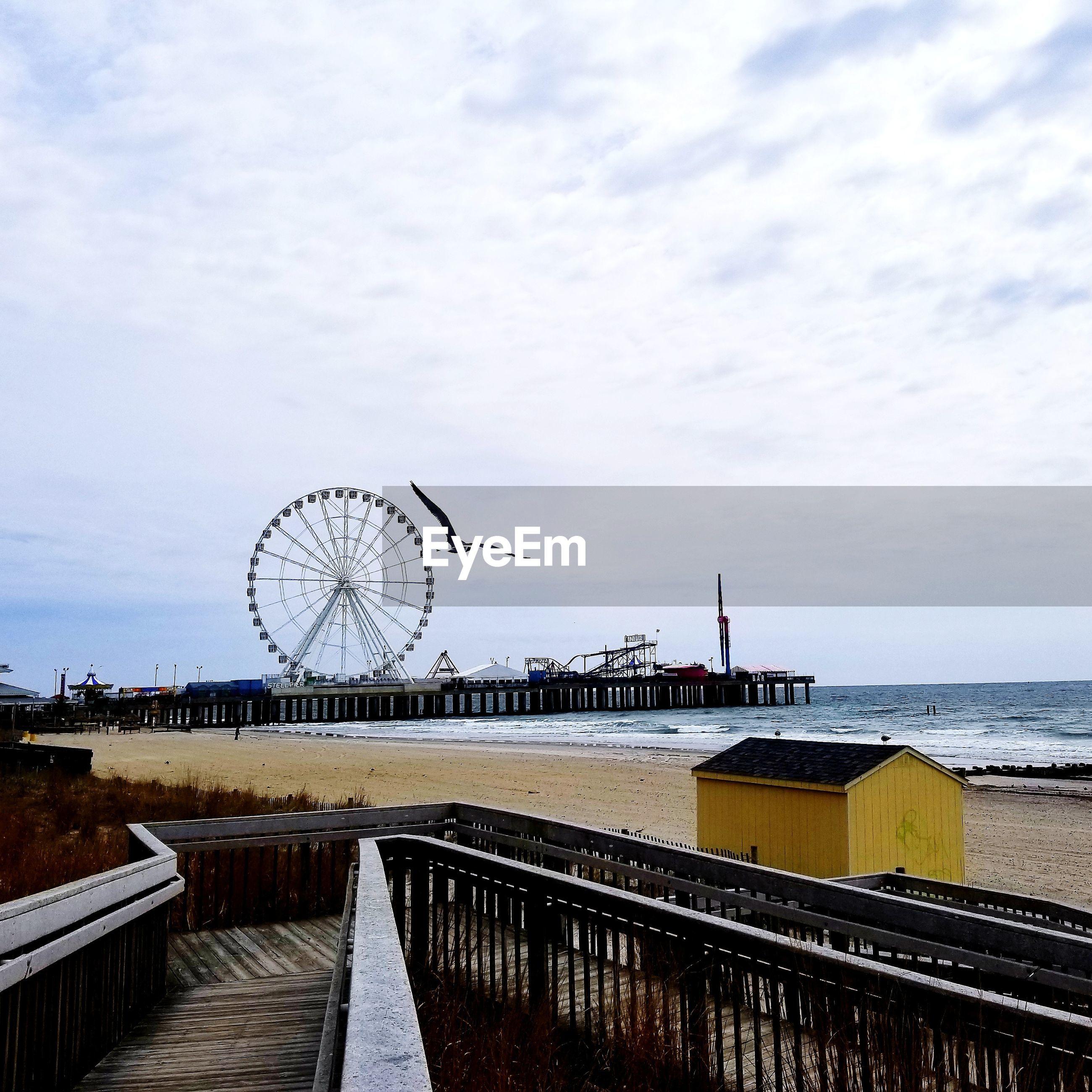 Ferris wheel by pier at sea against cloudy sky