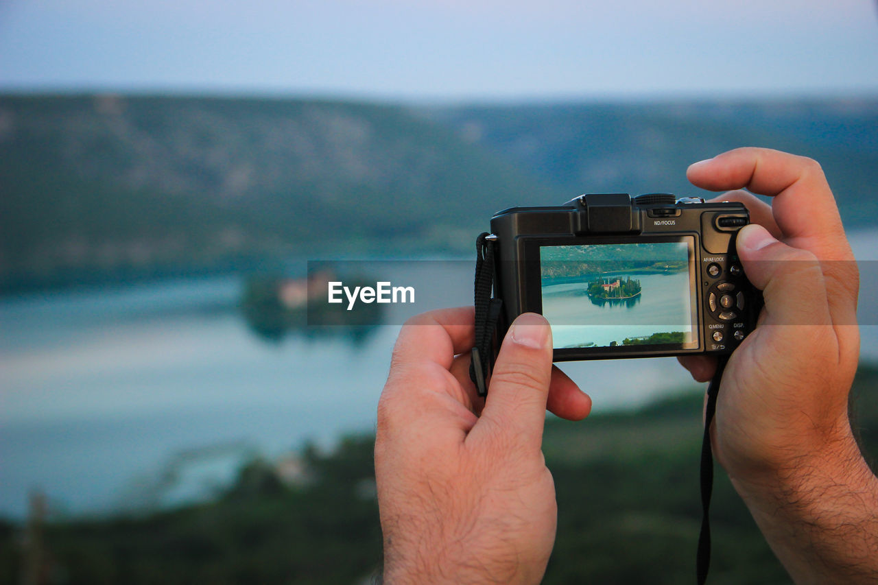 Cropped Image Of Man Hands Photographing Lake With Camera