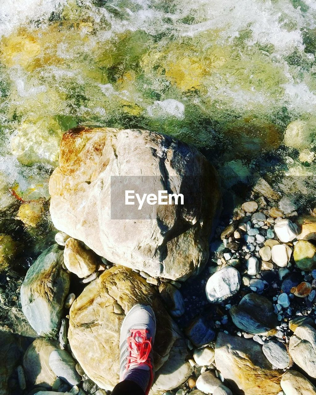 rock - object, personal perspective, pebble, human leg, one person, shallow, low section, water, standing, nature, real people, human body part, day, outdoors, beach, beauty in nature, close-up, pebble beach, people