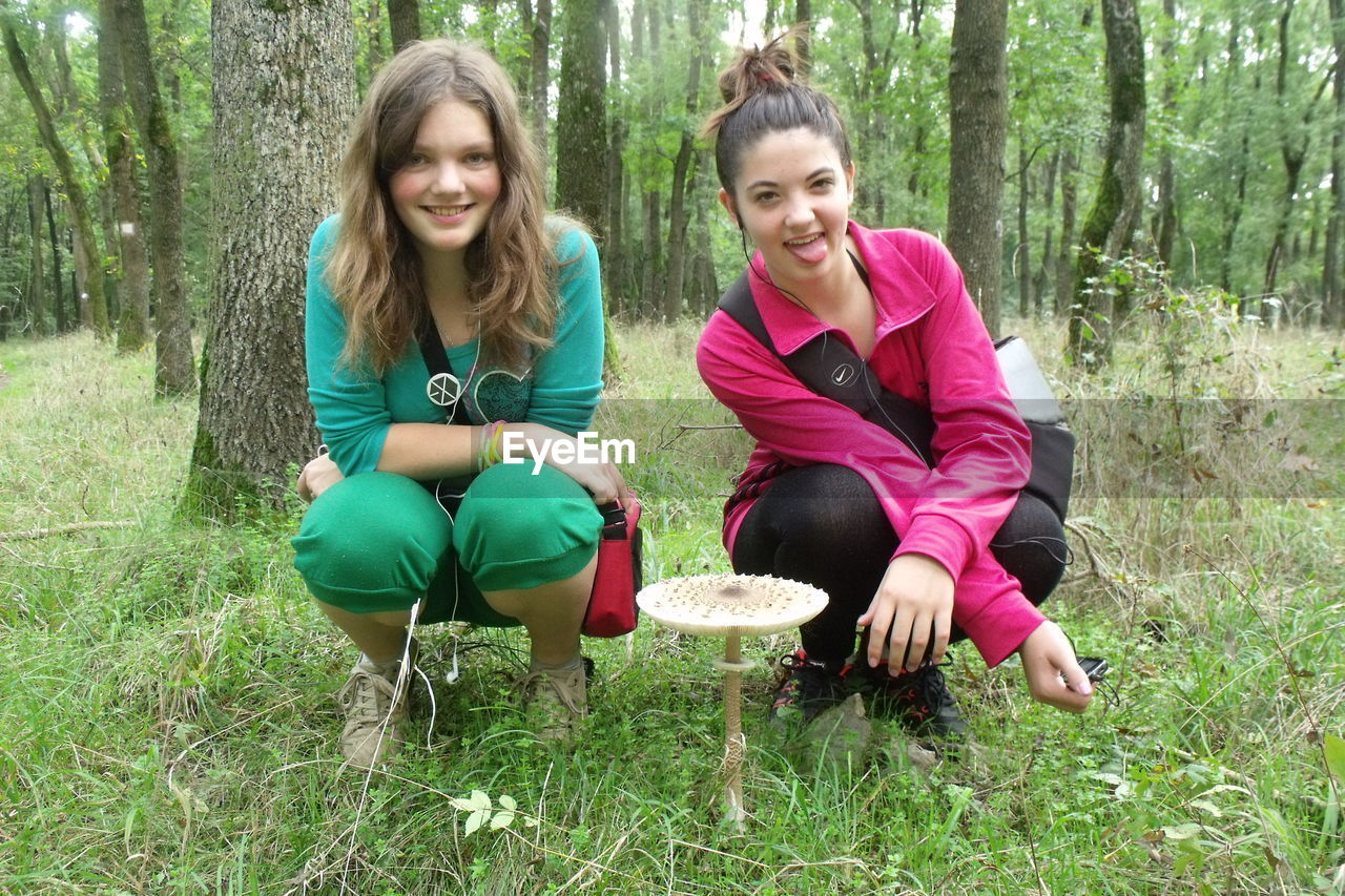 sitting, two people, togetherness, smiling, outdoors, full length, day, casual clothing, tree, nature, leisure activity, happiness, grass, looking at camera, forest, tree trunk, real people, portrait, girls, cheerful, bonding, growth, childhood, young women, beauty in nature, young adult, freshness, people, adult