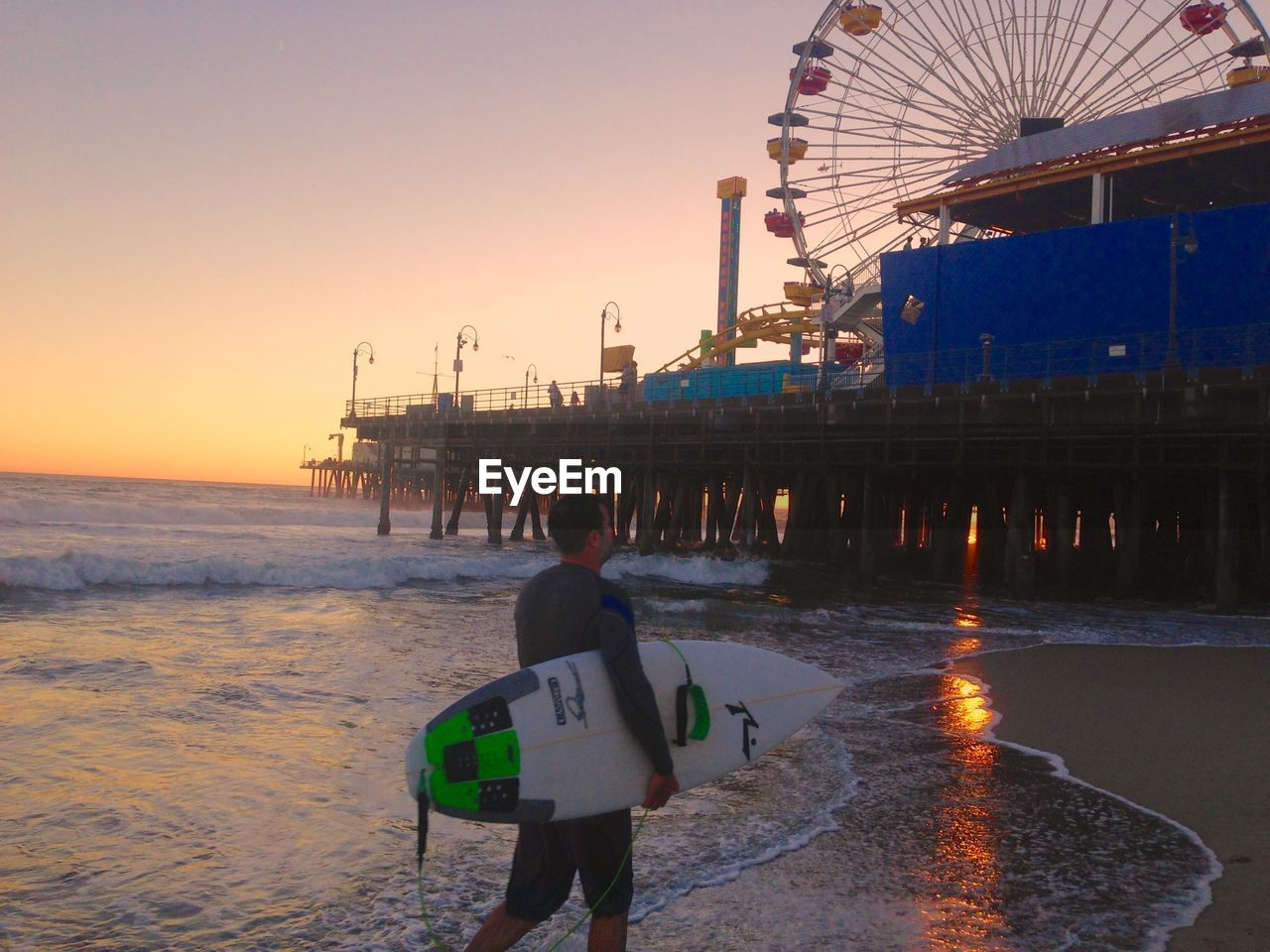 rear view, water, real people, leisure activity, sea, beach, amusement park, sunset, men, outdoors, clear sky, arts culture and entertainment, lifestyles, ferris wheel, vacations, nature, sky, full length, horizon over water, day, one person, people