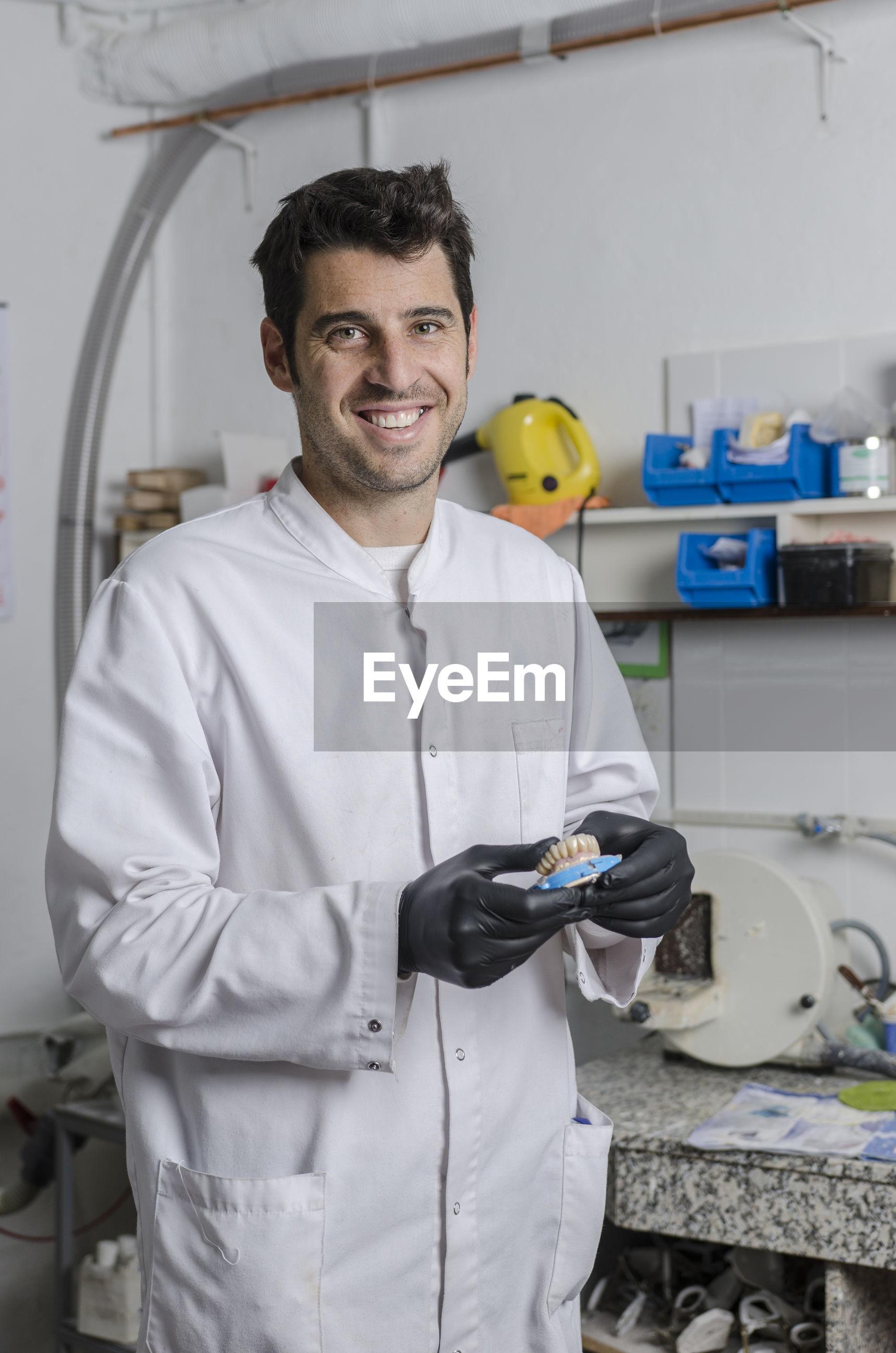 Portrait of smiling dentist holding dentures in laboratory