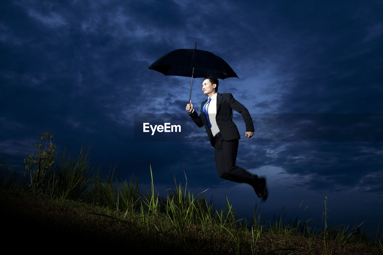 Businessman holding umbrella while flying on land against storm clouds