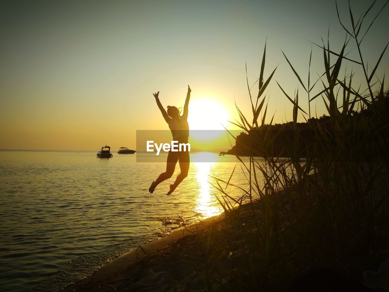 sky, sunset, water, silhouette, mid-air, one person, jumping, leisure activity, lifestyles, real people, human arm, arms raised, sea, beauty in nature, nature, scenics - nature, tranquil scene, limb, horizon over water, outdoors, freedom, human limb