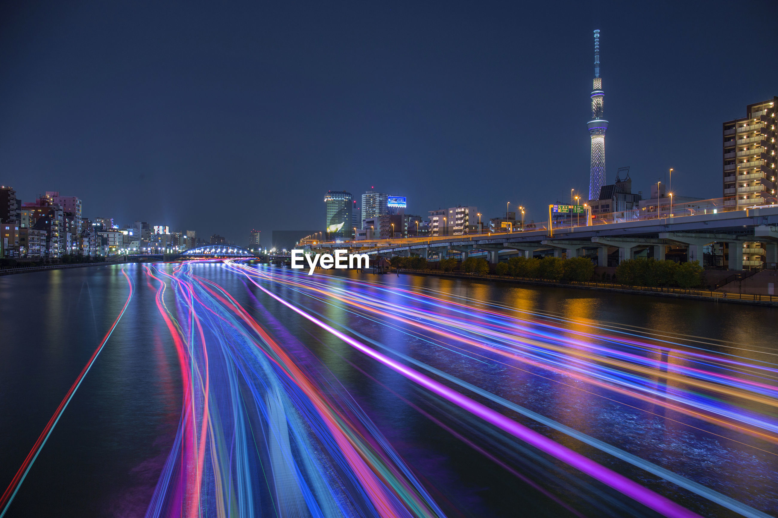 LIGHT TRAILS AMIDST BUILDINGS IN CITY AT NIGHT