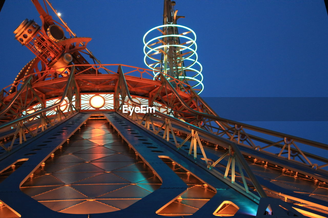 Low Angle View Of Illuminated Roller Coaster Against Blue Sky