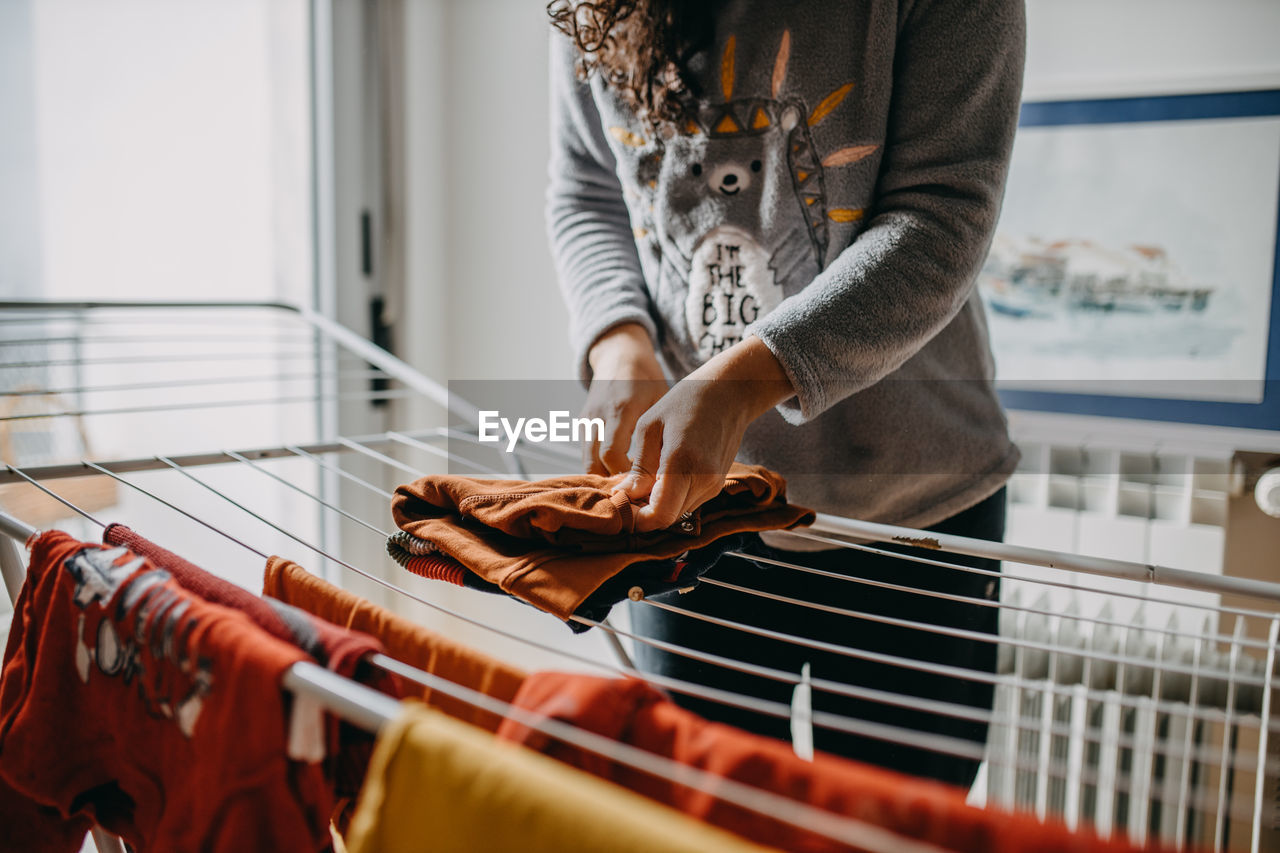 Midsection of woman holding clothes on clothesline at home