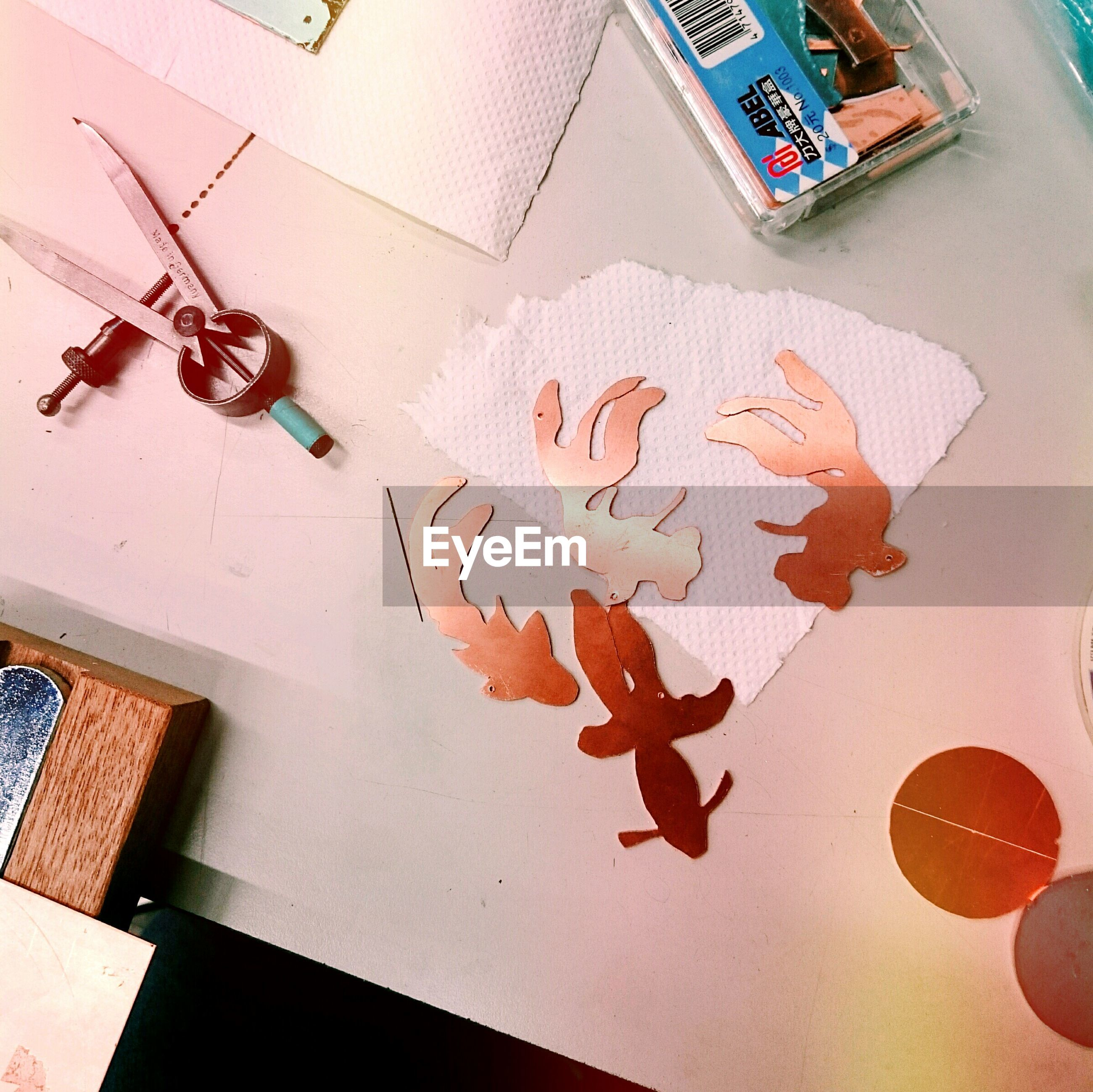indoors, creativity, art and craft, art, high angle view, wall - building feature, multi colored, animal representation, text, paper, table, still life, craft, flooring, communication, western script, drawing - art product, no people, painting, human representation
