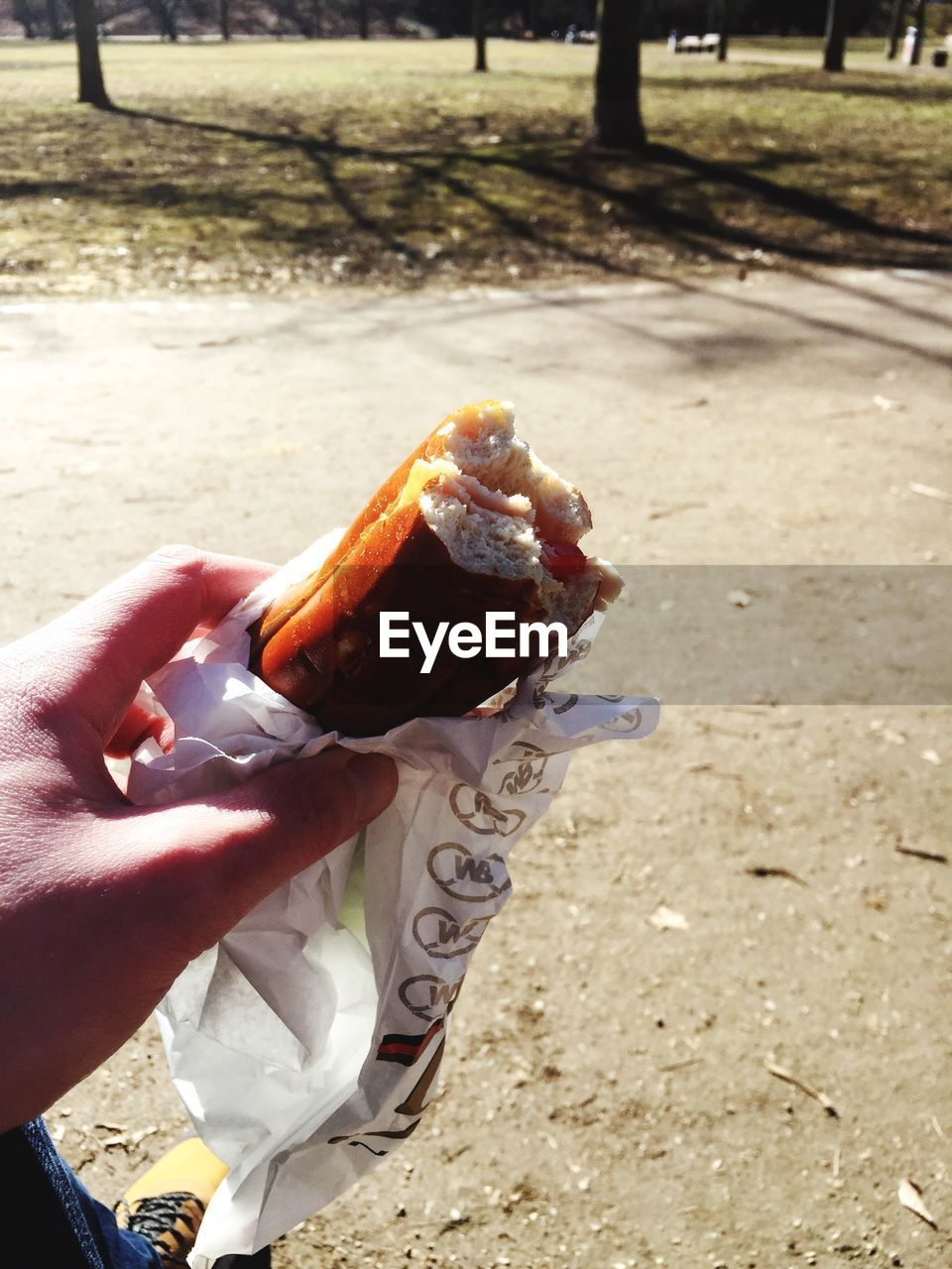 human hand, human body part, one person, holding, real people, food and drink, food, human finger, outdoors, unhealthy eating, take out food, day, lifestyles, women, close-up, freshness, eaten, eating, fast food, hot dog, ready-to-eat, people